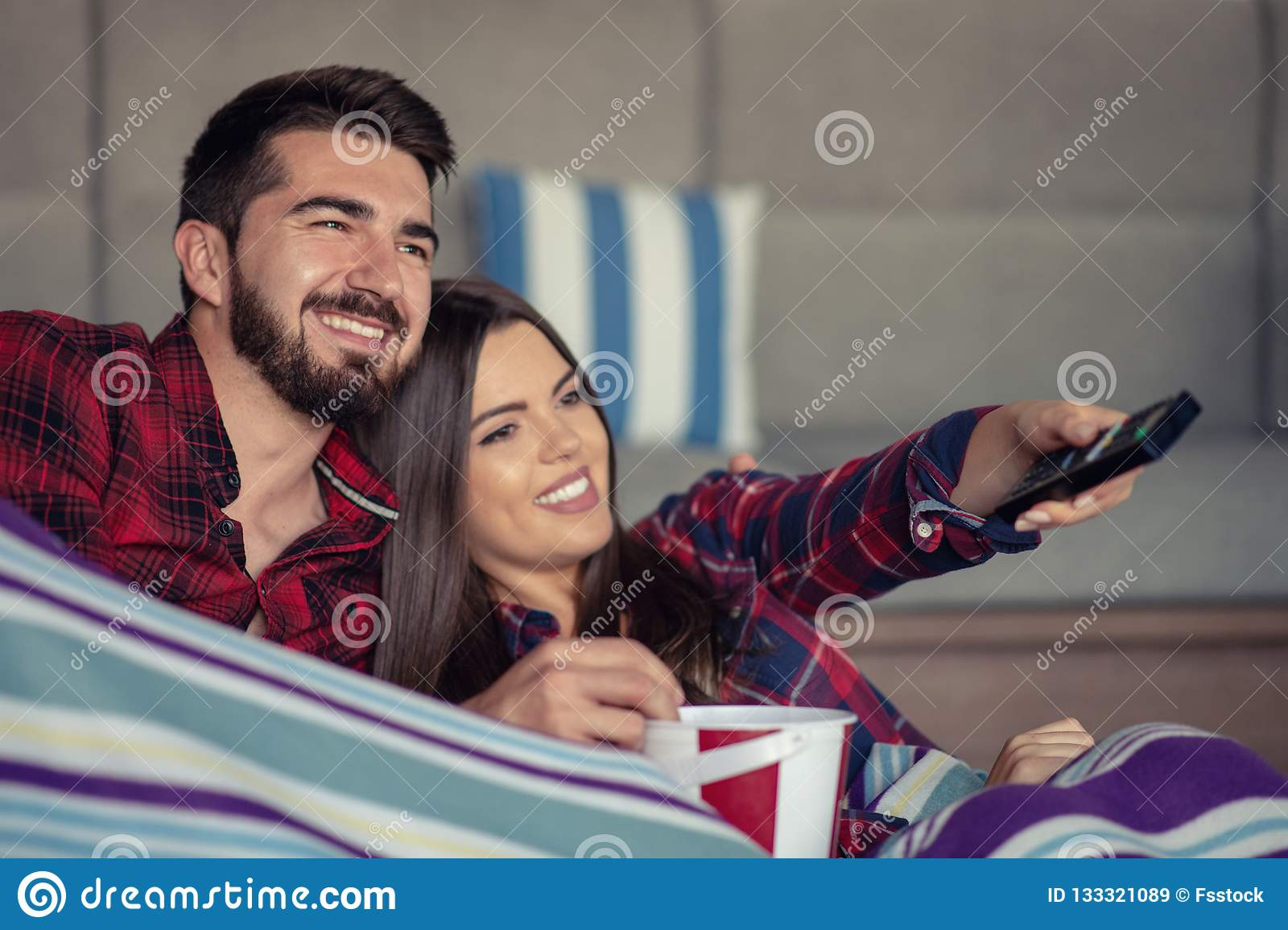 Couple in love enjoying their free time, sitting on a couch next to the window, playing video games and having fun.