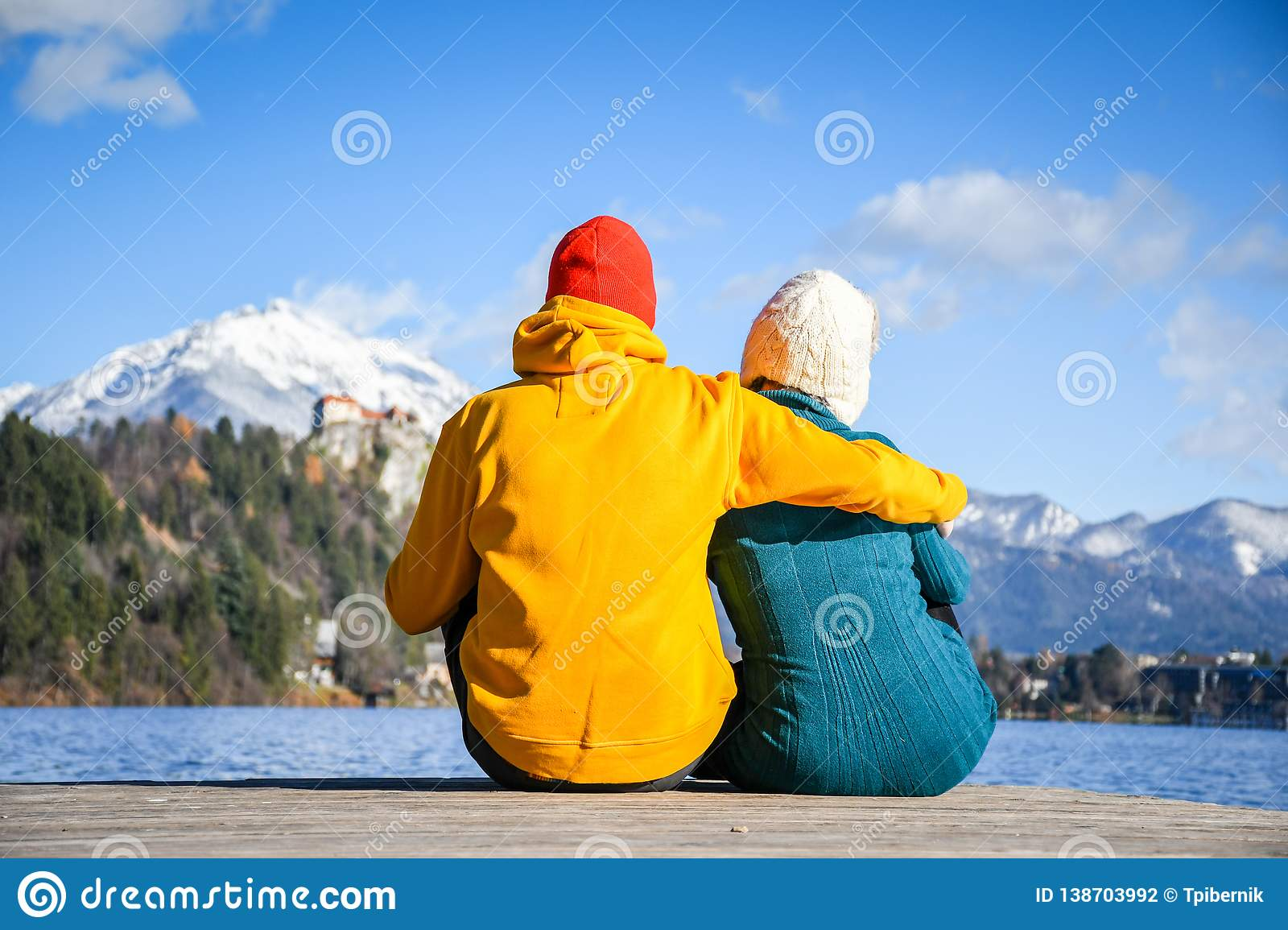 Couple in love hugging together with colorful cloths sitting and relaxing on a wooden pier on a clear sky sunny winter day view fr