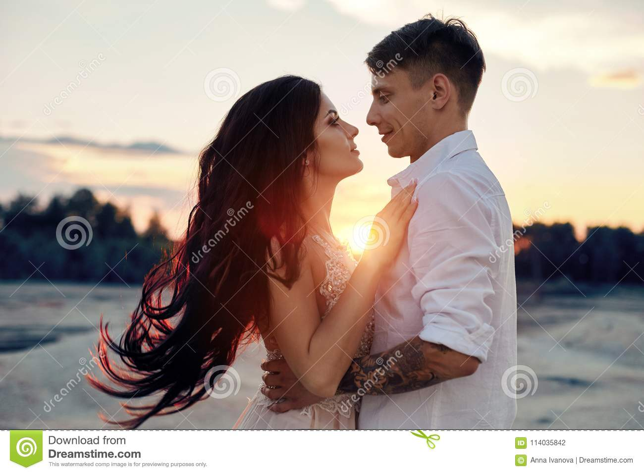 Couple in love hugs kiss happy life, man and woman, the sunset, the sun rays, a couple in love looking each other in the eye.