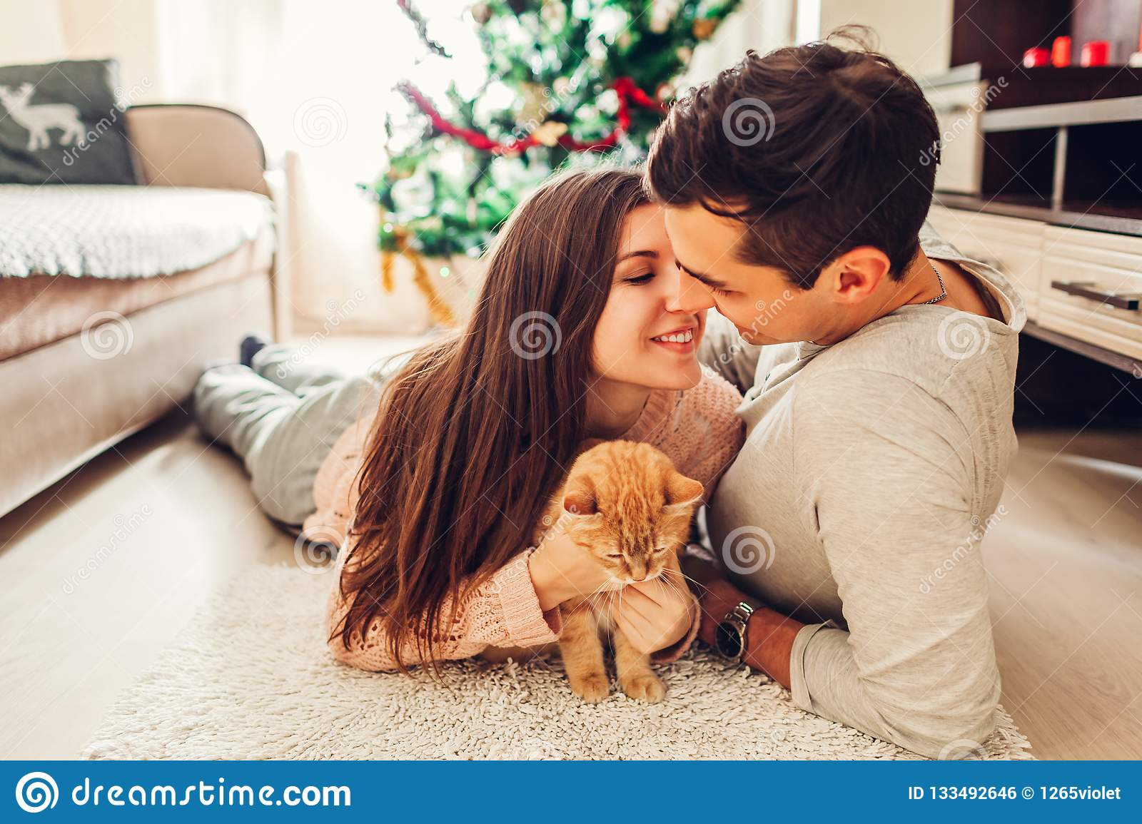 Couple in love lying by Christmas tree and playing with cat at home. Man and woman kissing