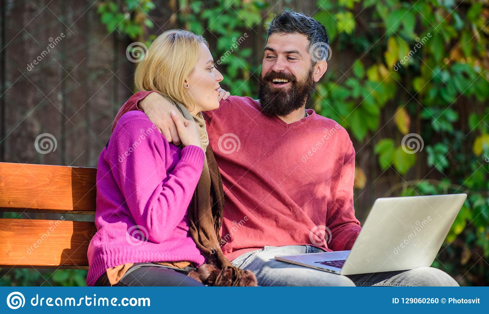 Couple in love notebook consume content. Surfing internet together. Couple with laptop sit bench in park nature