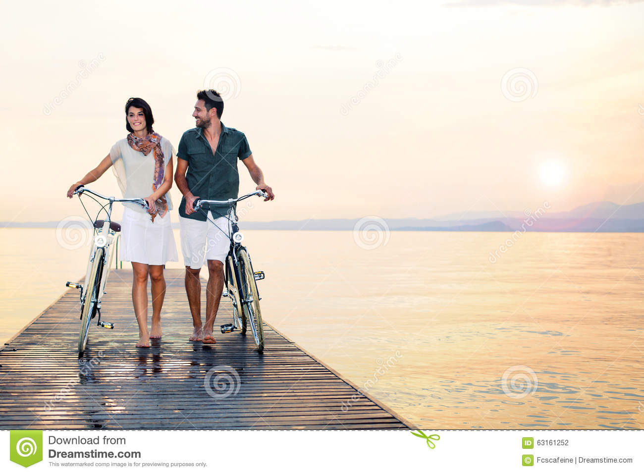 Couple in love pushing bike on a boardwalk at the sea
