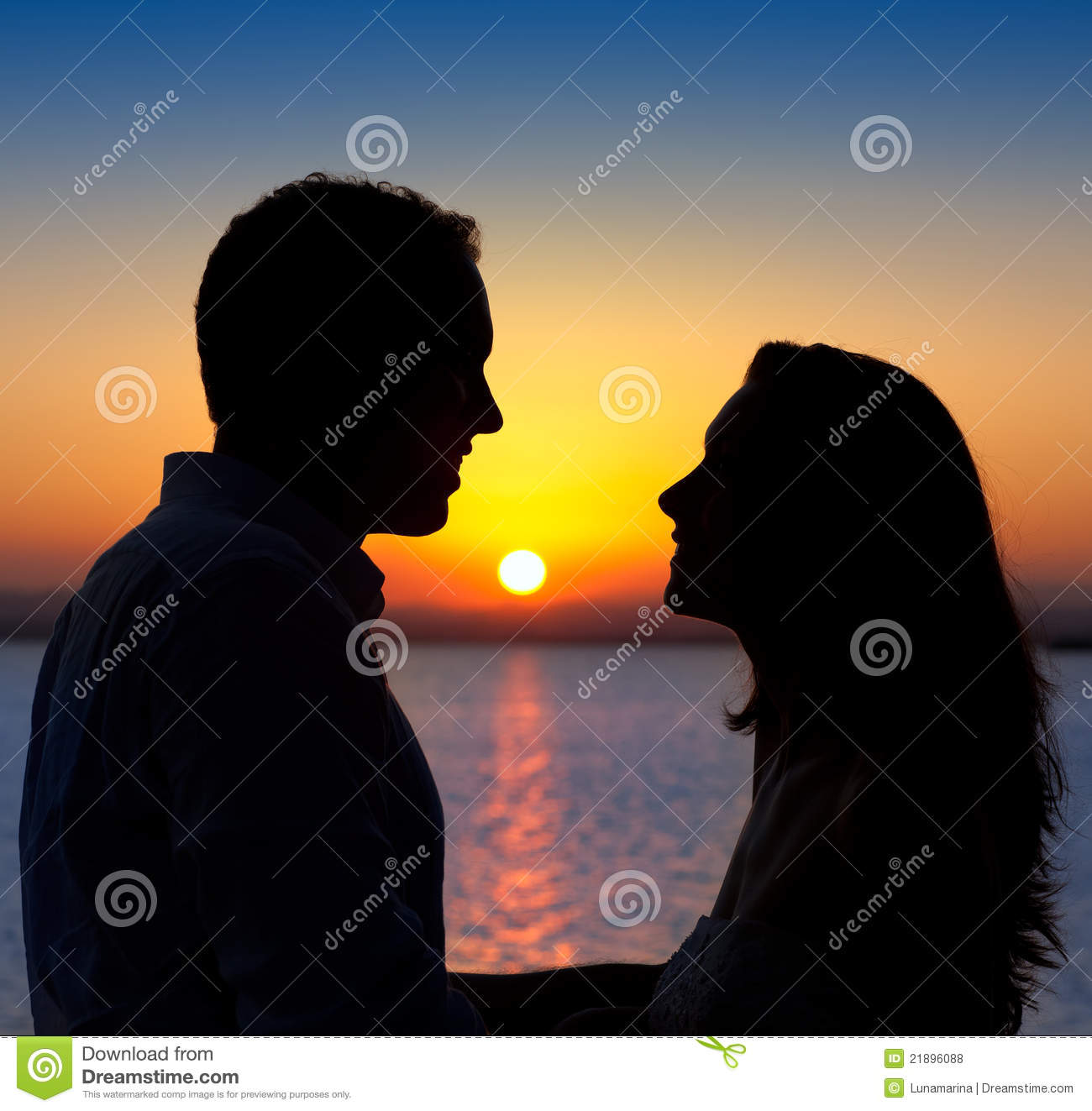 Happy Couple Sitting On Sandy Beach Embracing Kissing: Couple In Love Silhouette At Lake Sunset Royalty Free