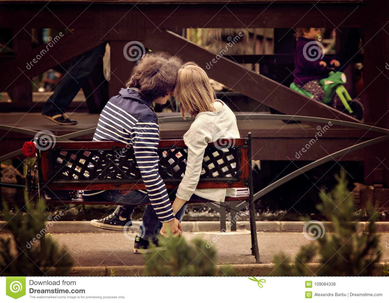 Young couple holding hands on bench in park.