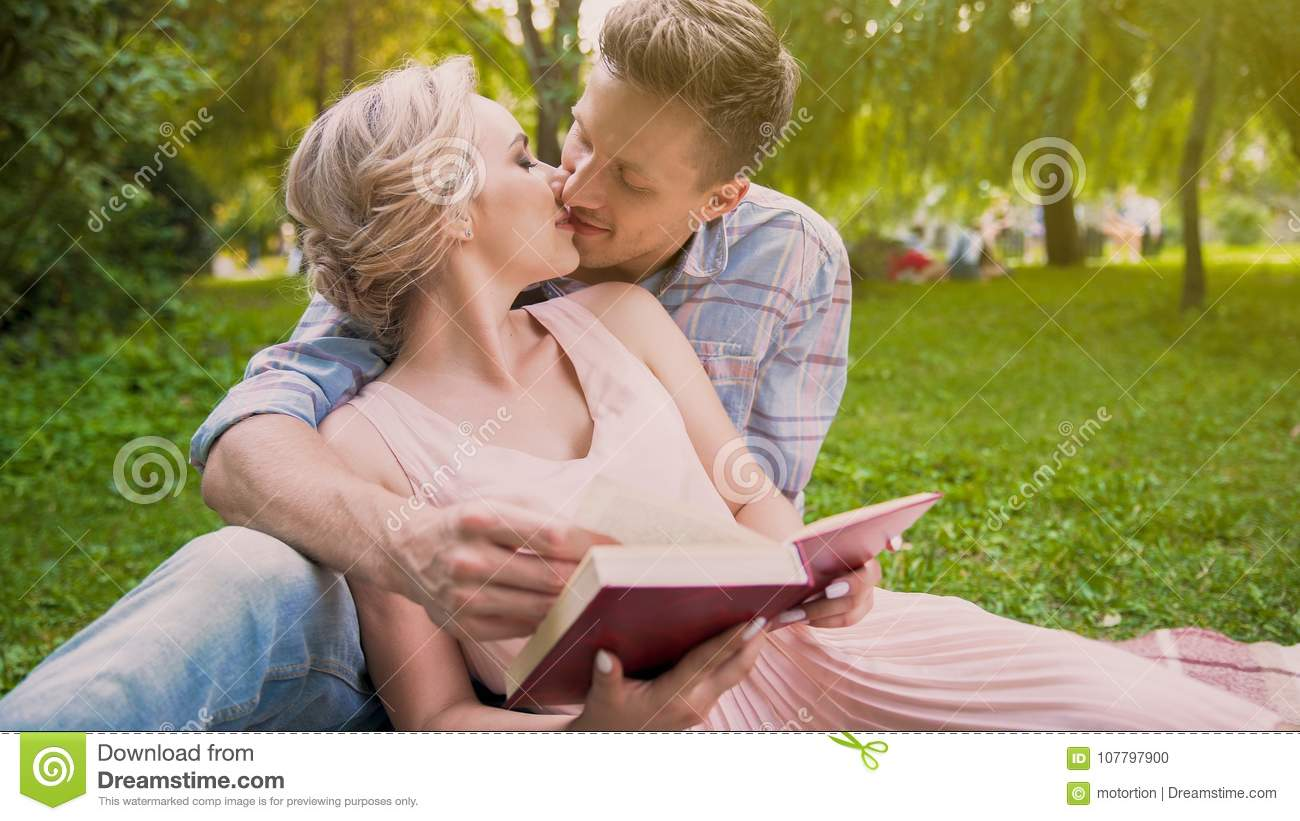Couple in love sitting on rug reading book together, gently kissing in breaks