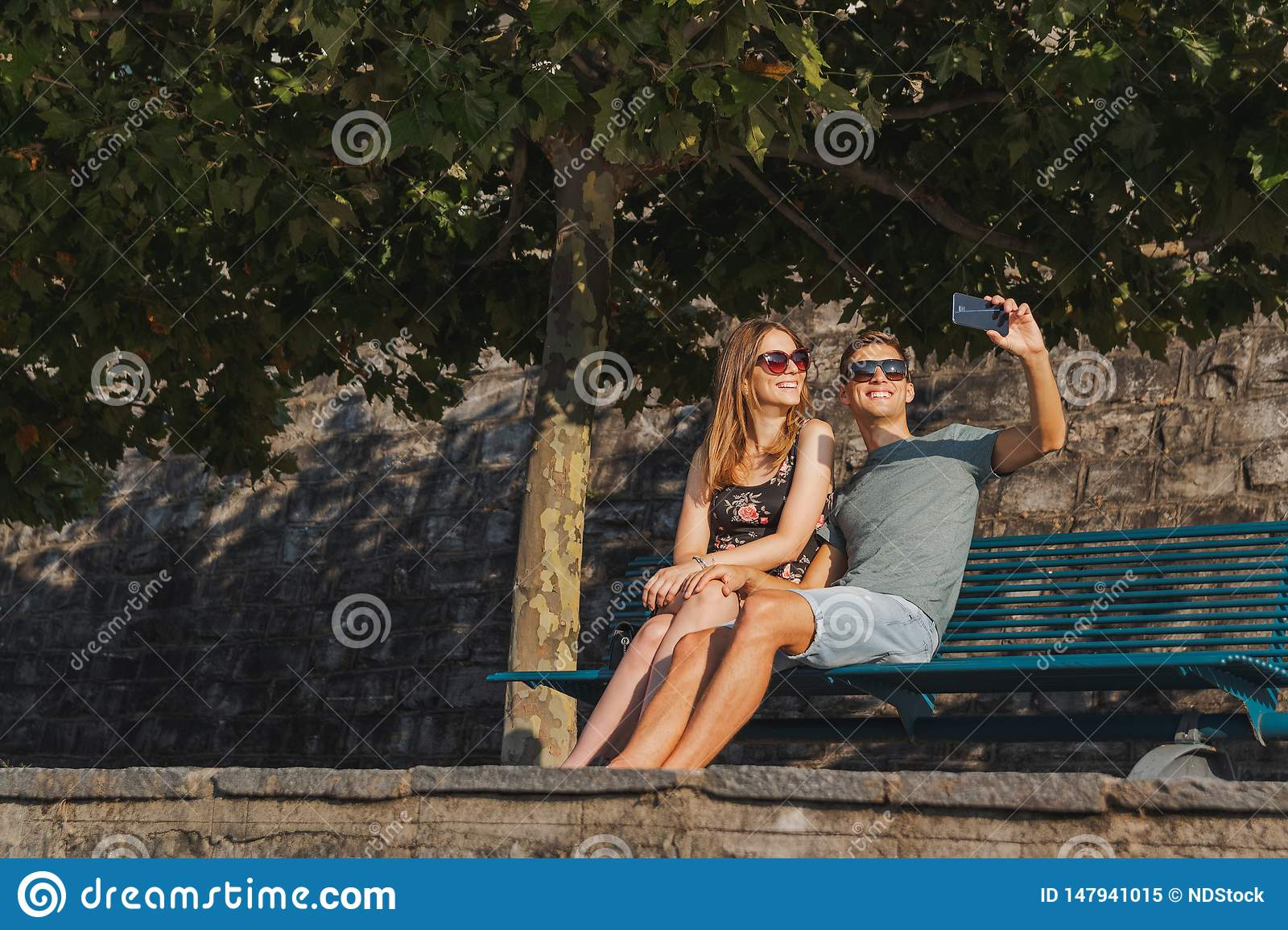 Young couple in love seated on a bench taking a selfie and relaxing during a sunny day