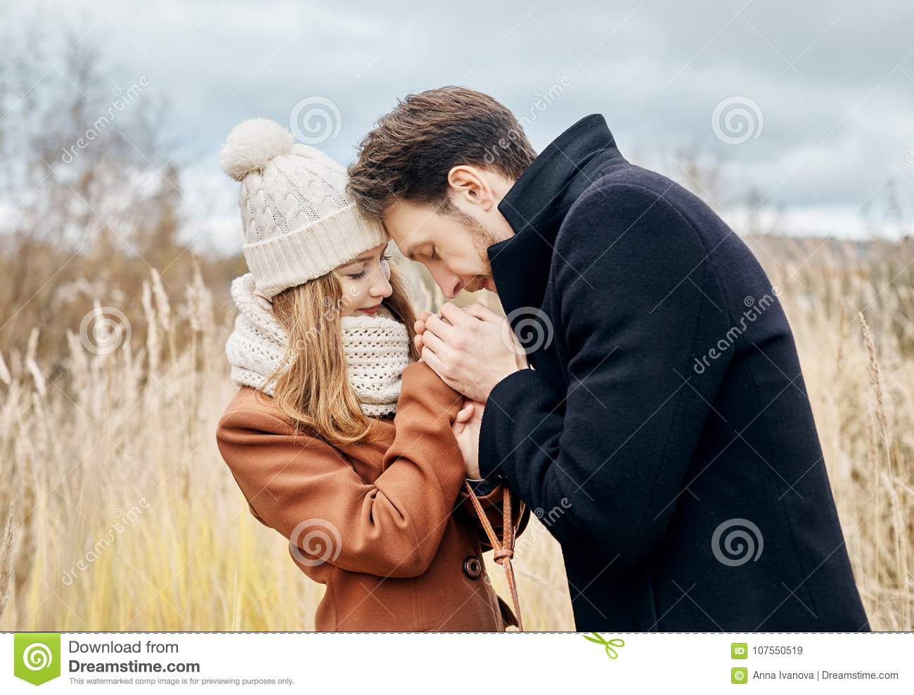 Couple in love walking in the autumn Park, cool fall weather. A man and a woman embrace and kiss, love and affection yellow autumn