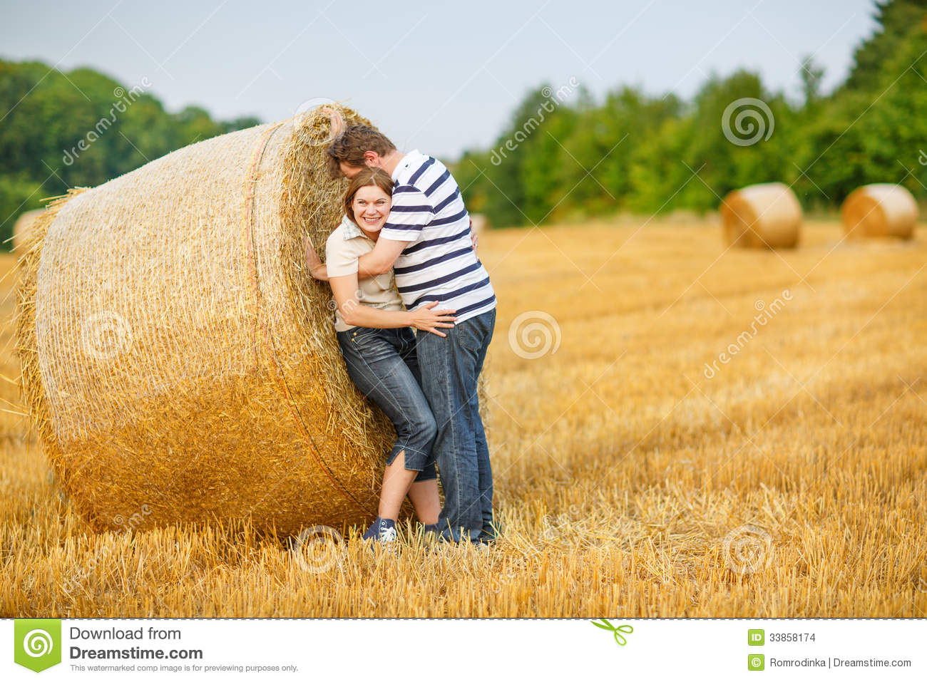 couple in love on yellow hay field on summer evening.