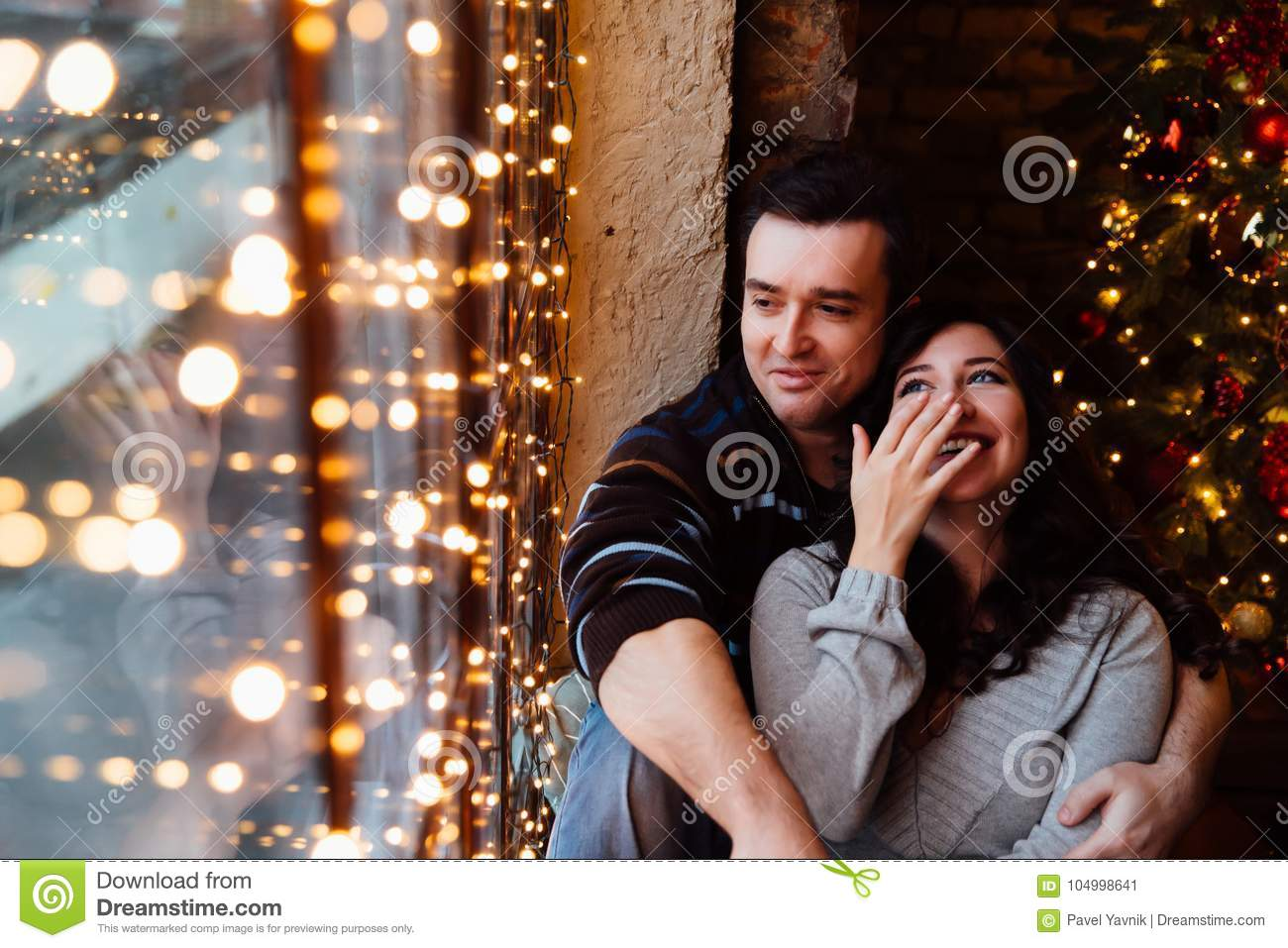 The Christmas Loft.Couple Of Lovers Hugs Sitting On The Windowsill In The