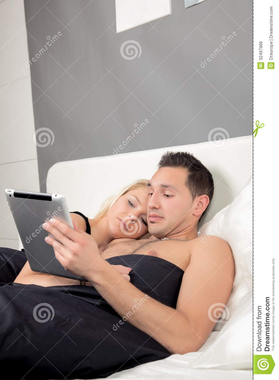 couple lying in bed reading a tablet pc stock photo image of loving leisure 32497966. Black Bedroom Furniture Sets. Home Design Ideas