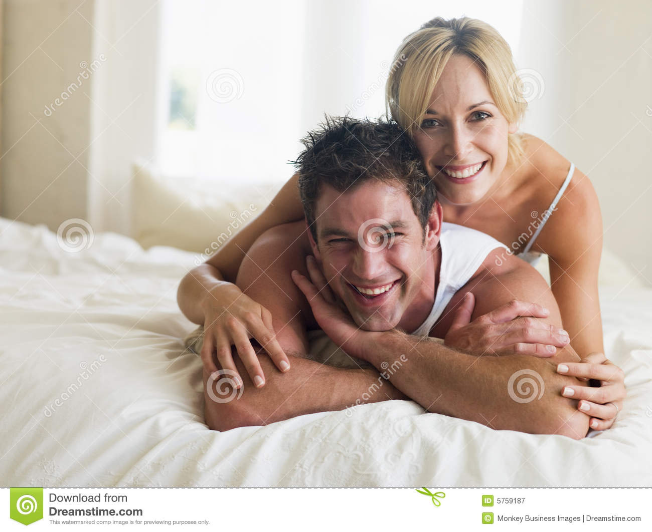 couple lying in bed smiling royalty free stock photography image 5759187. Black Bedroom Furniture Sets. Home Design Ideas