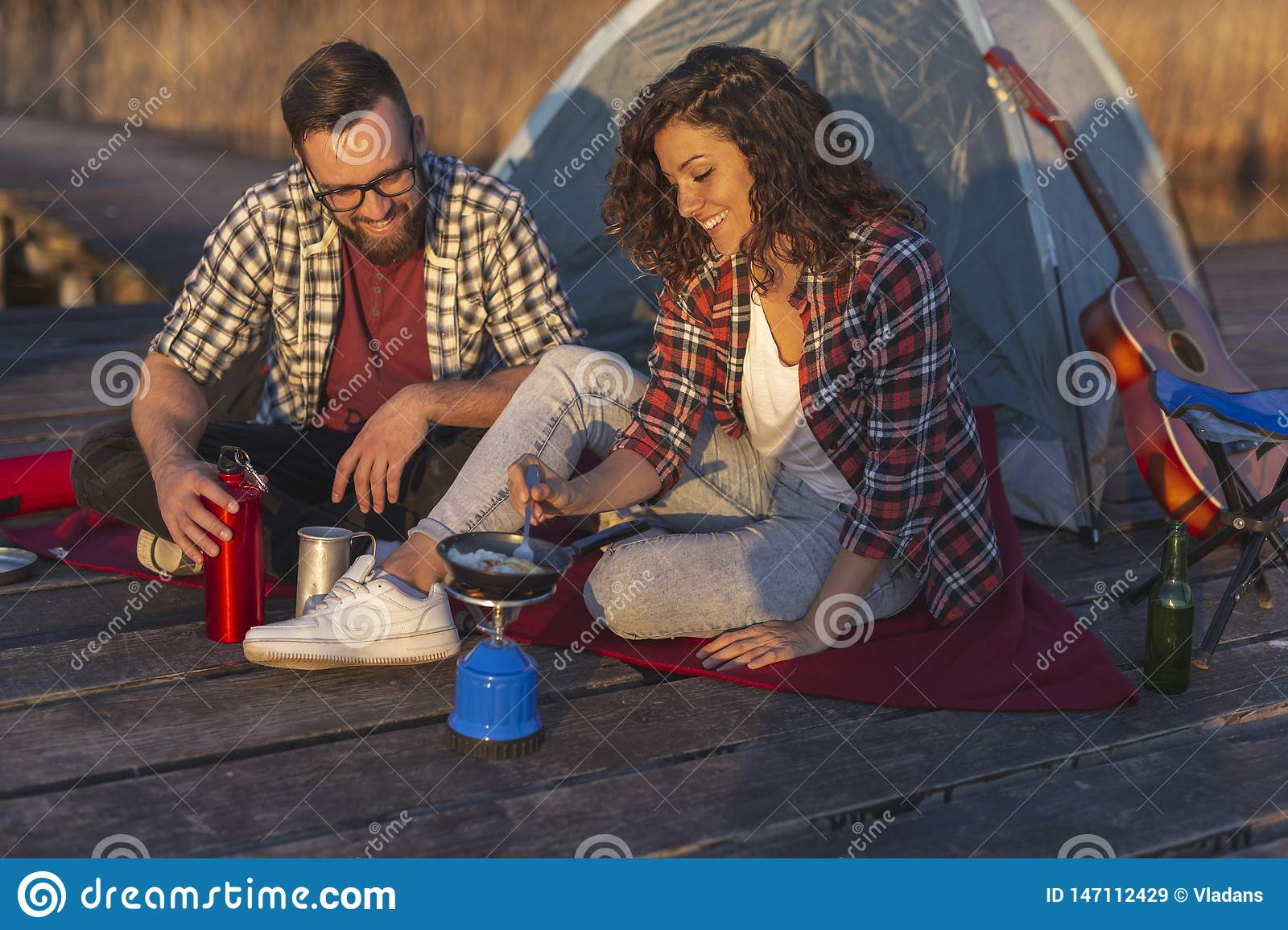 Couple making breakfast while camping