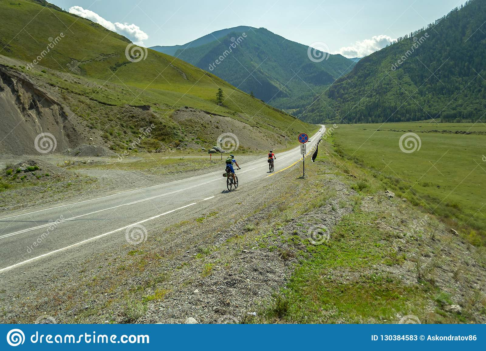 A couple of man and woman in helmets ride on sports bicycles on