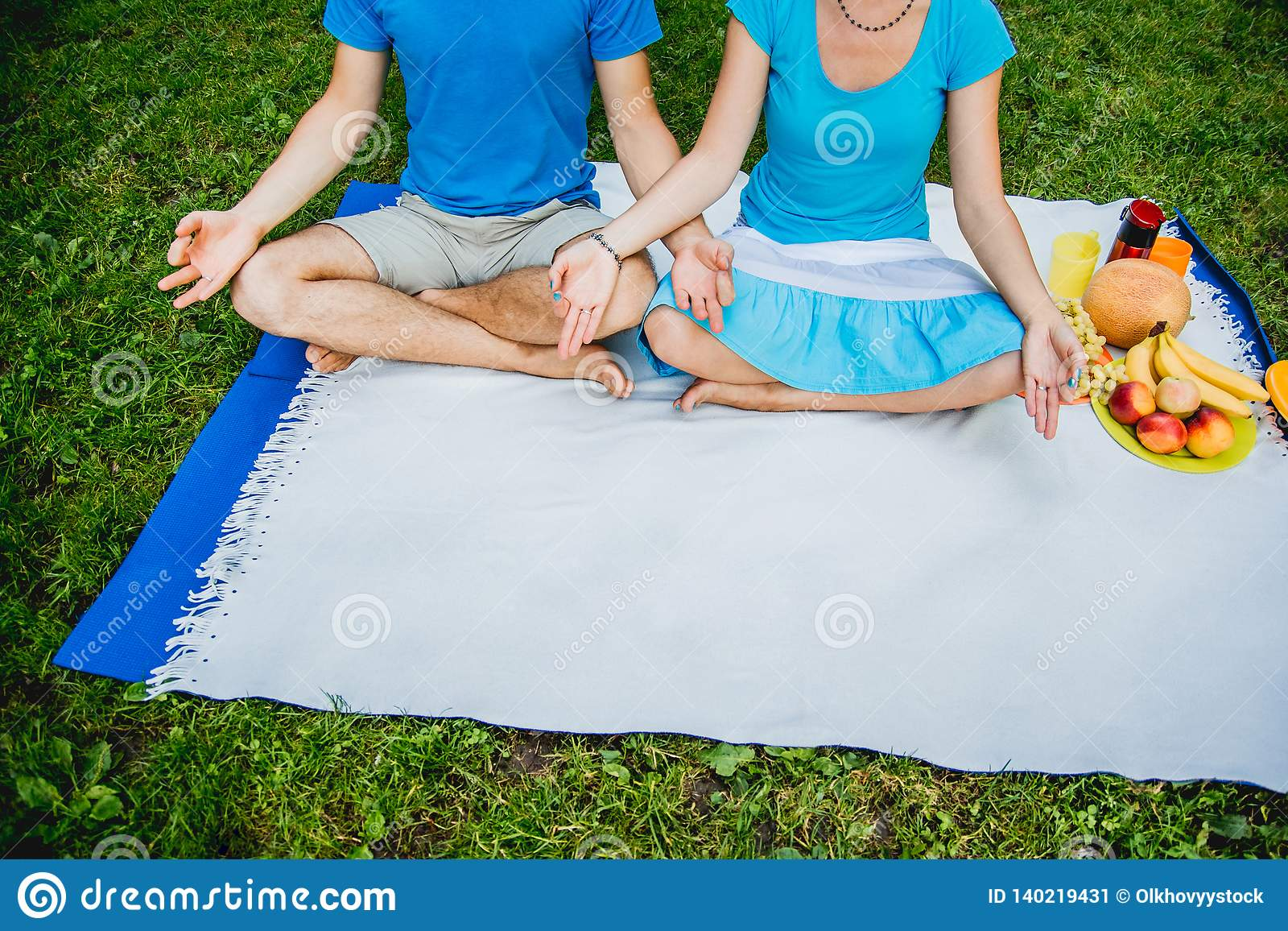 Couple man and woman sitting on the meadow with green grass in the Lotus position. Meditate in peace and freedom