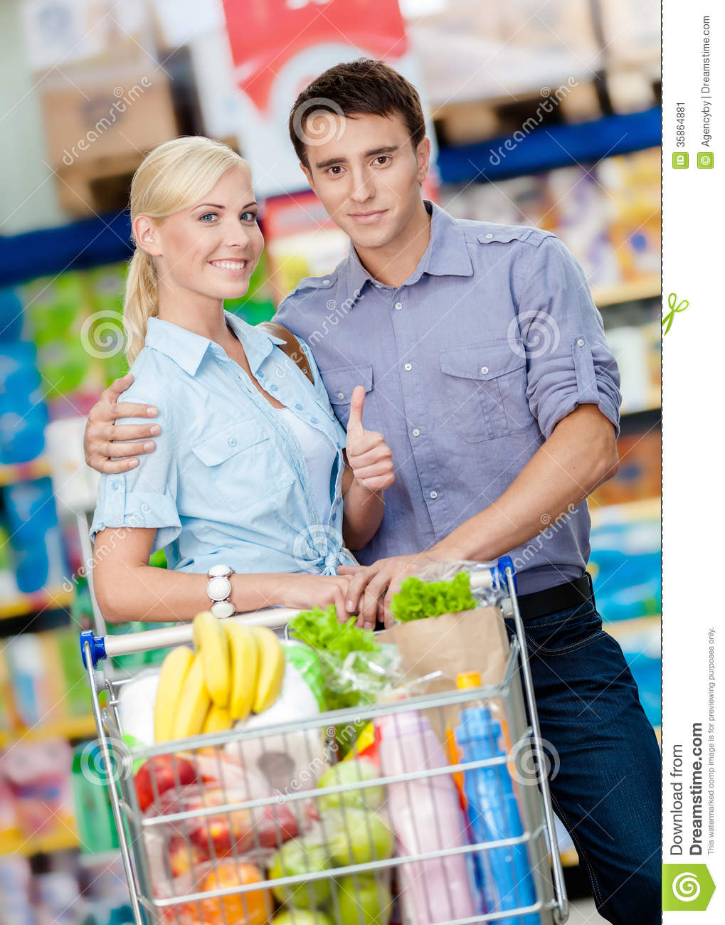 Couple In The Market With Cart Full Of Food Stock Image