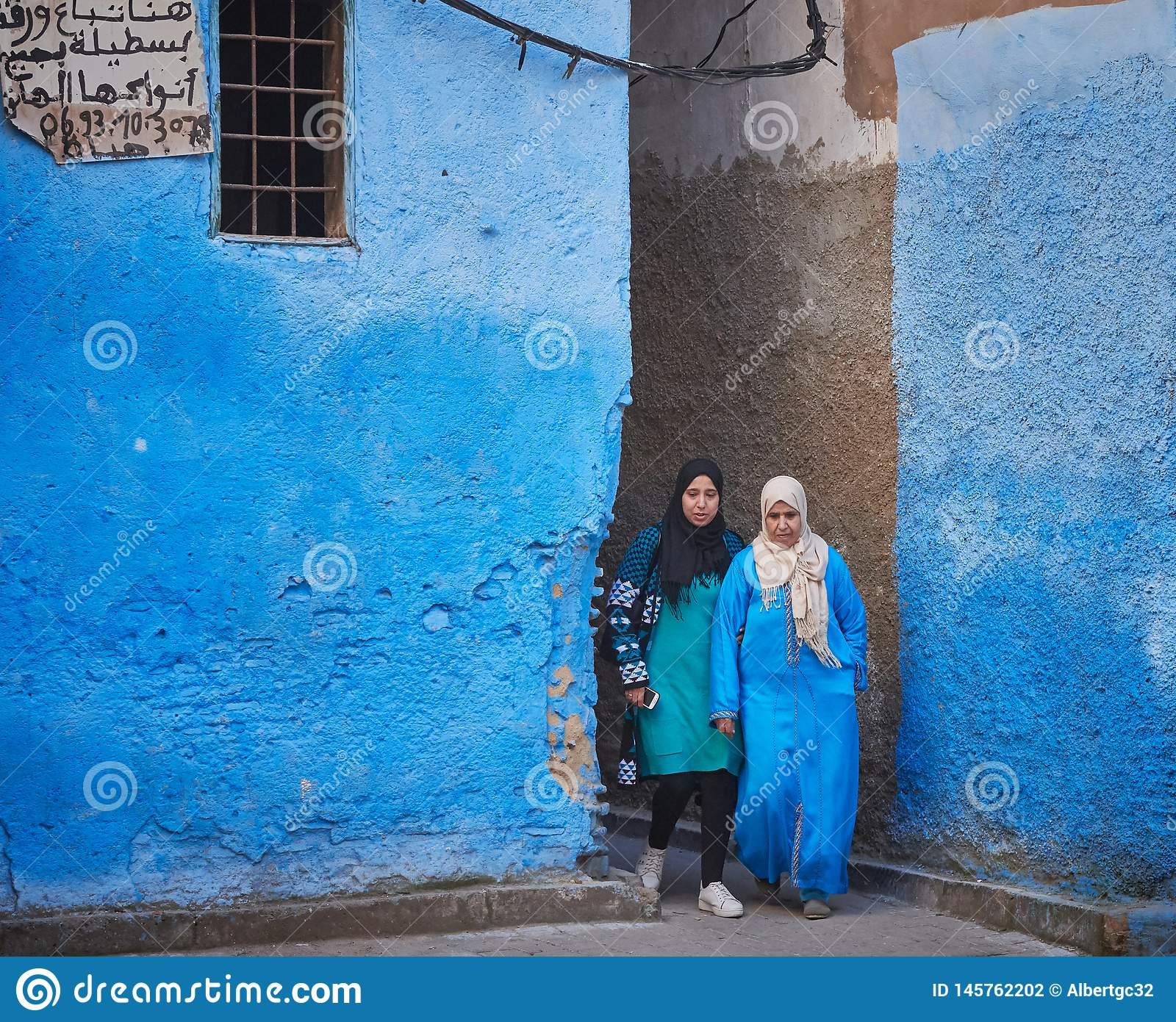 Fez, Morocco - December 07, 2018: couple of Moroccan women leaving a blue alley in the medina of fez