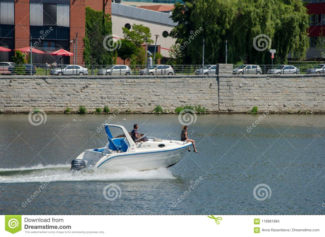 A couple in a motor boat in the river. Woman sit on rostrum of a