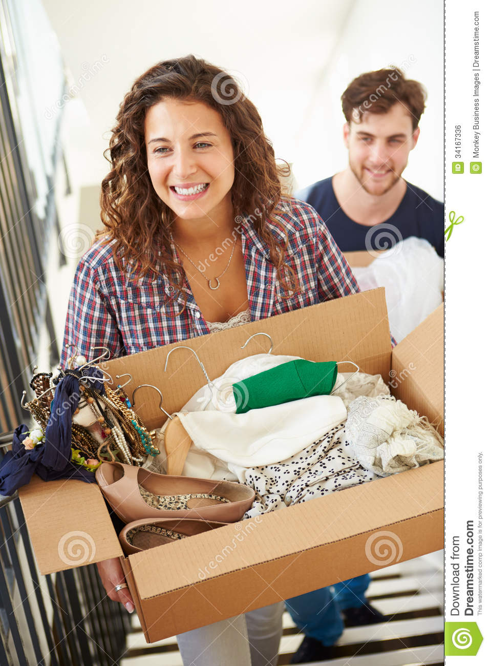 Couple Moving Into New Home Carrying Box Upstairs
