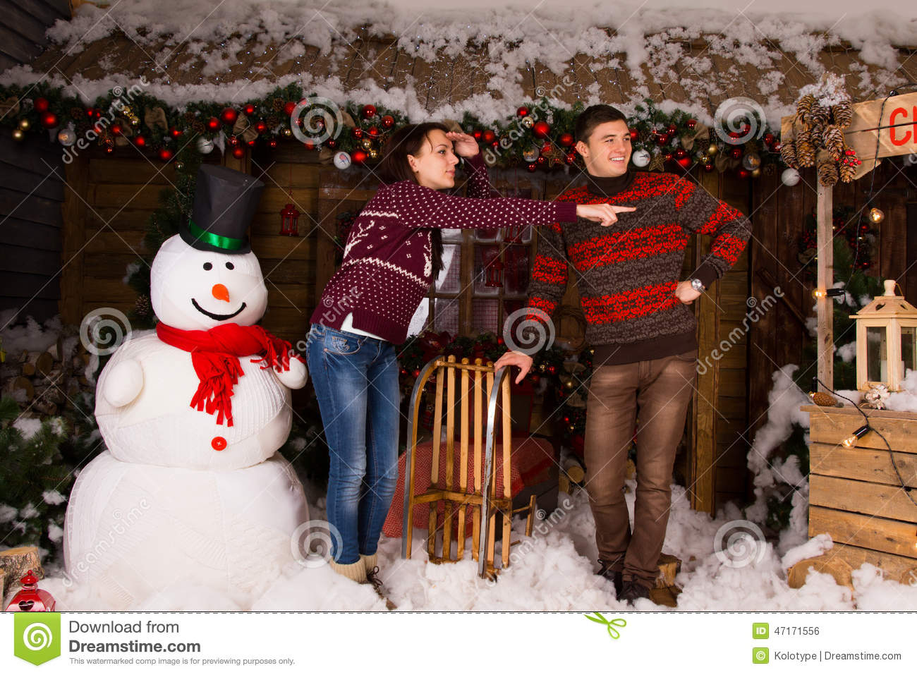 couple near indoor snowman looking at right frame