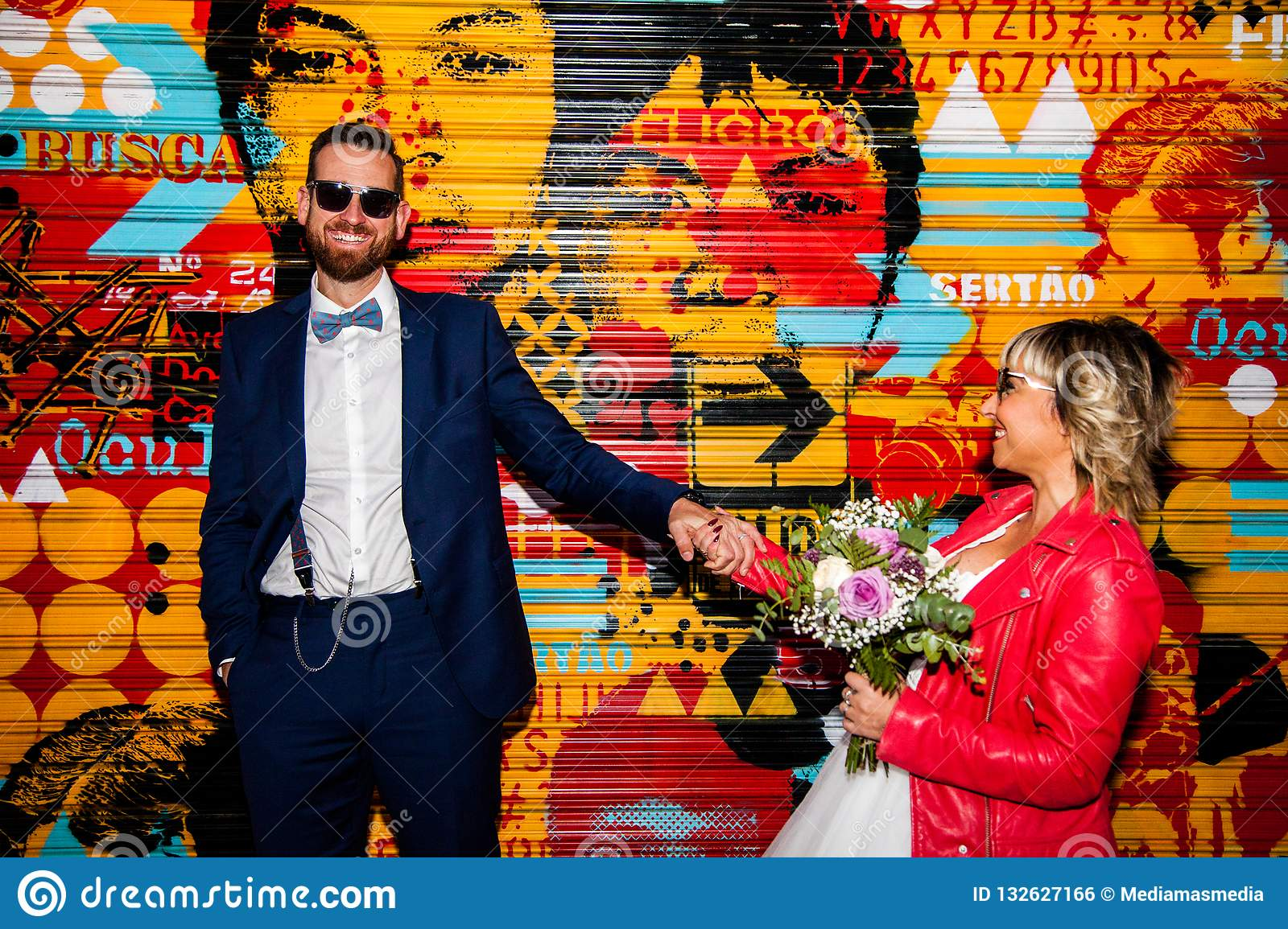 Couple of newlyweds pose in front of a graffiti metal blind