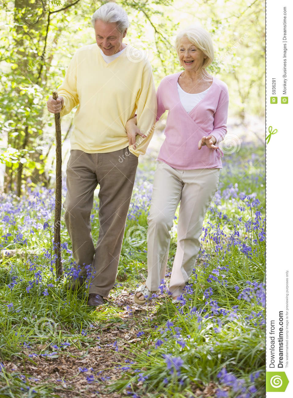 Couple outdoors smiling stick walking