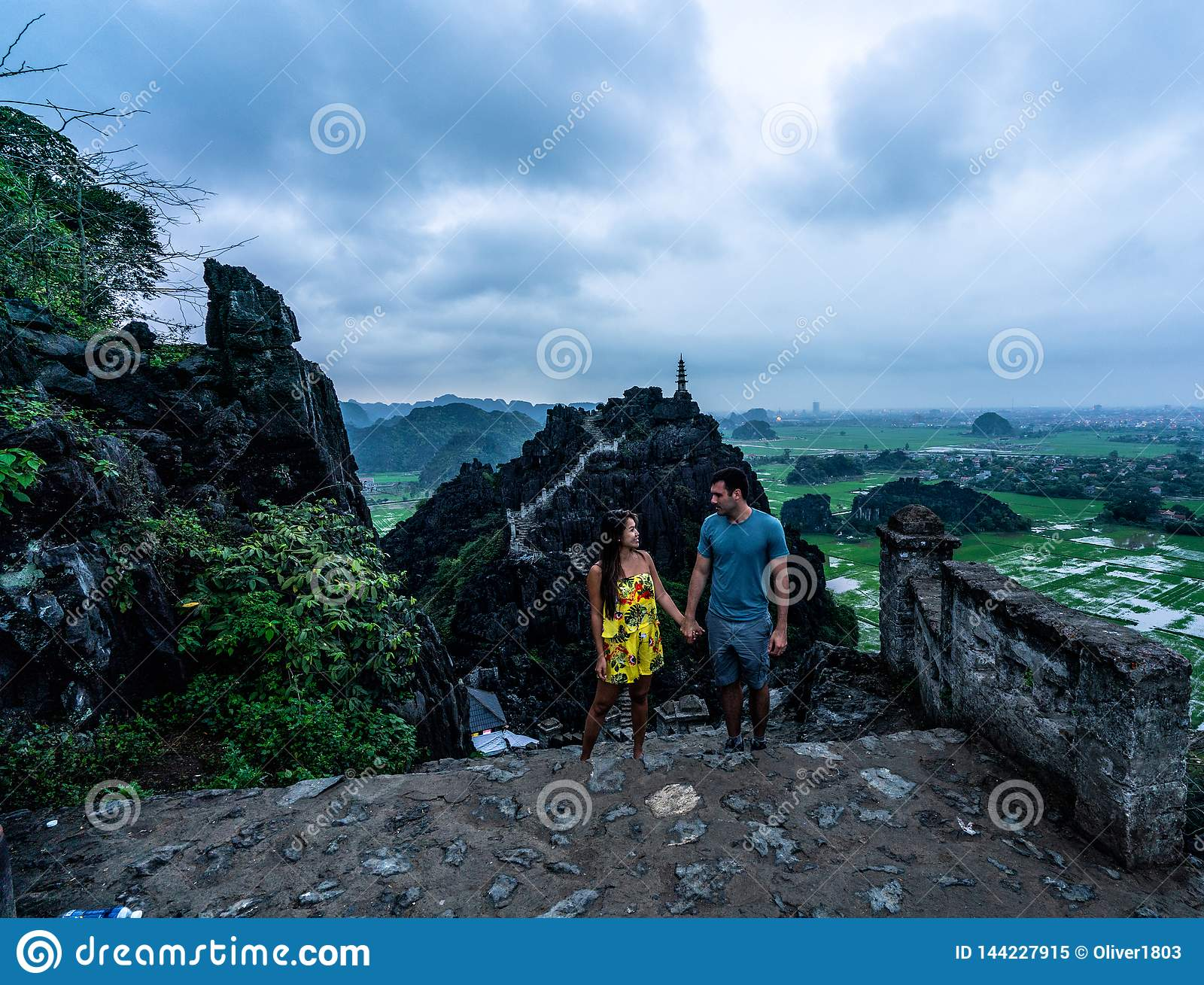 A couple overlooks the mountains of northern Vietnam from Hang Mua, a popular hiking destination.