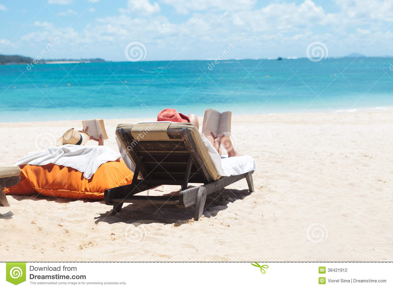 Couple Of People Reading While Sunbathing On The Beach ...