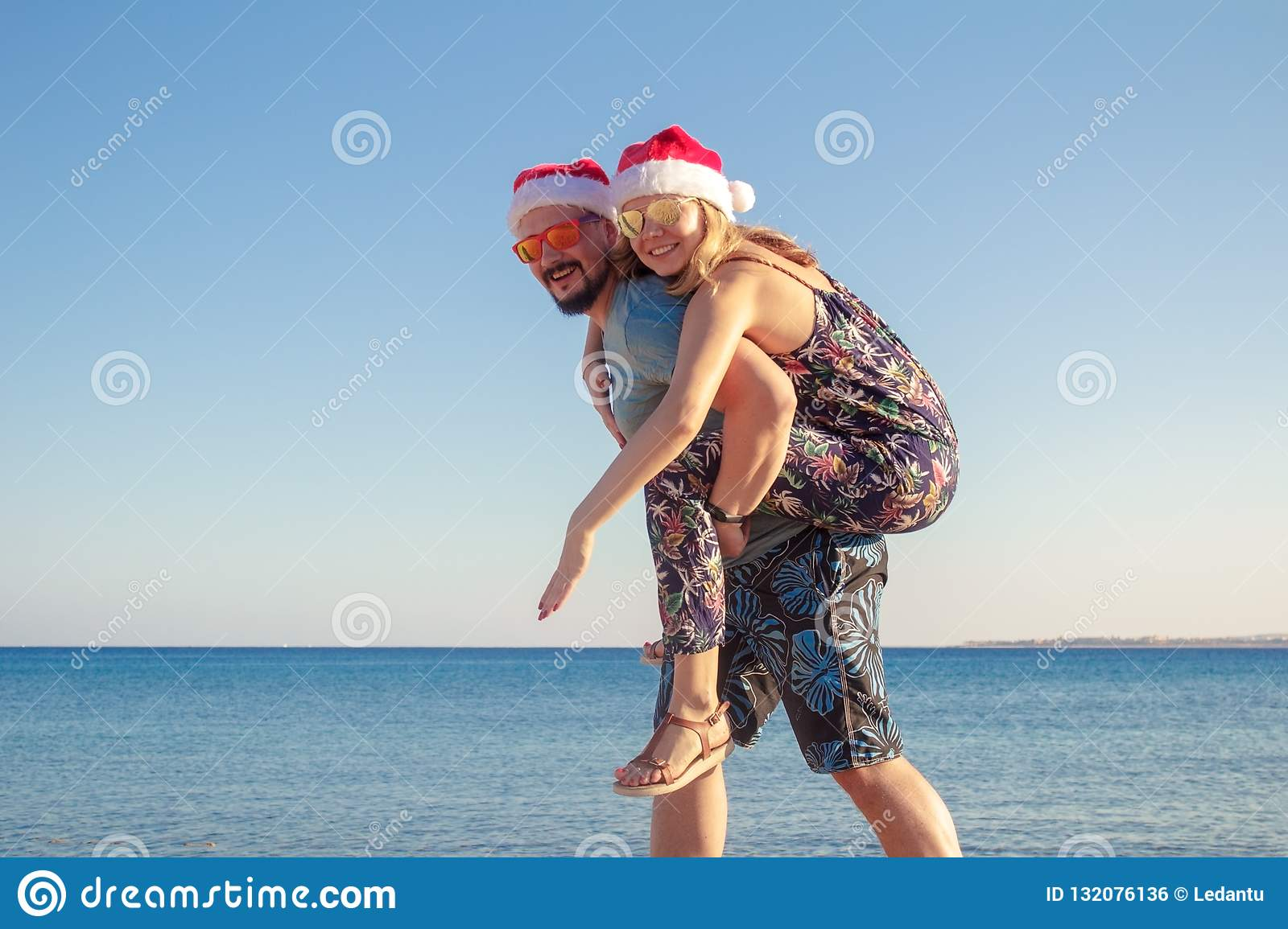 02daac30 Couple piggybacking in christmas hats and sunglasses at the beach of the sea .