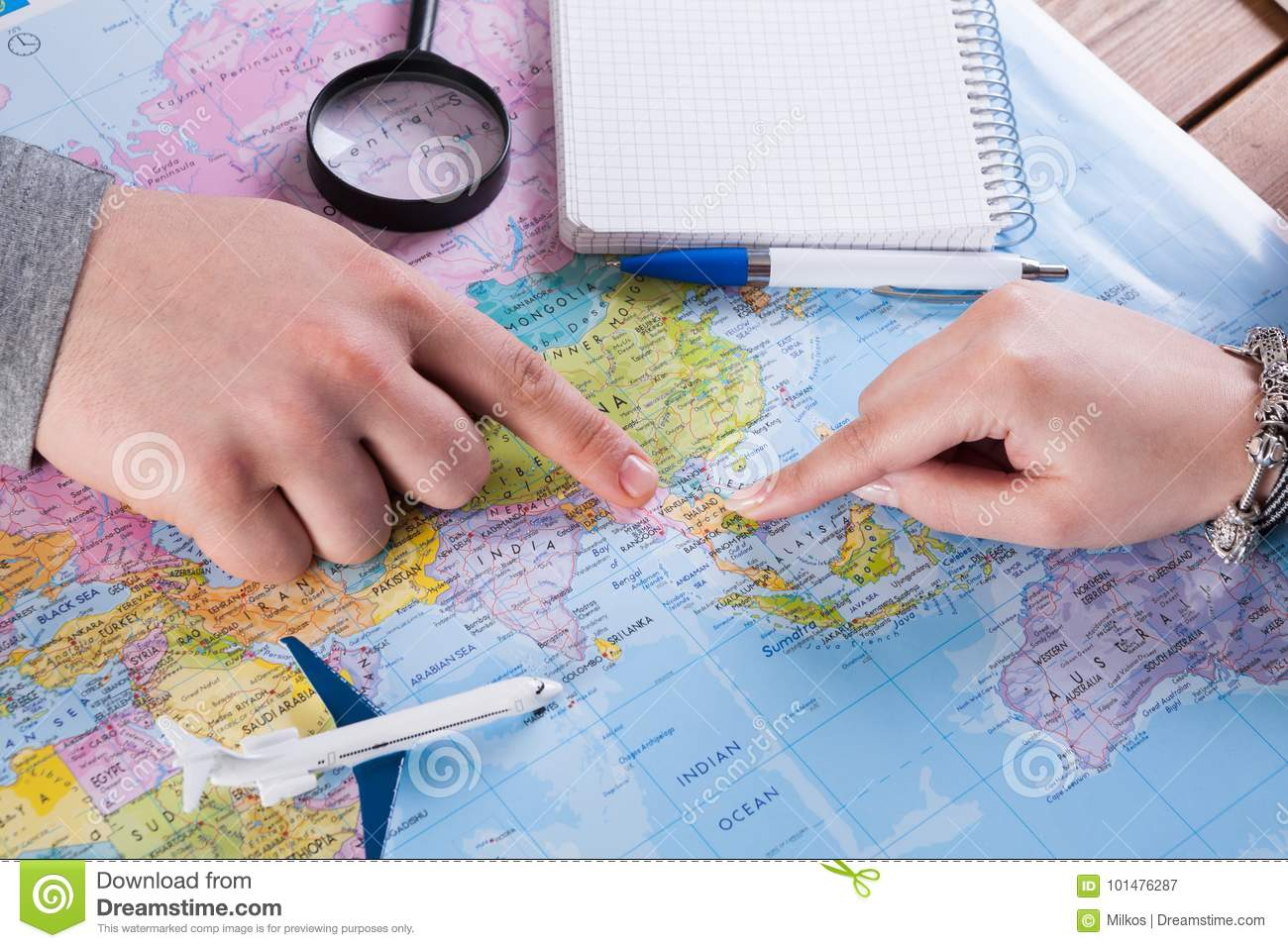 Couple planning trip to Thailand, point on map