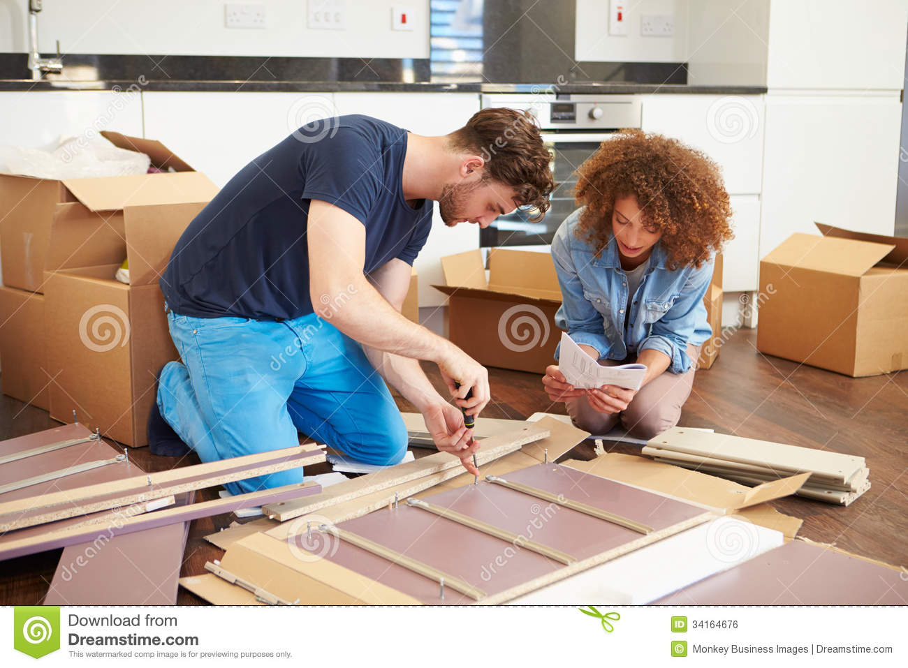 Couple Putting Together Self Assembly Furniture In New Home Royalty Free  Stock Image