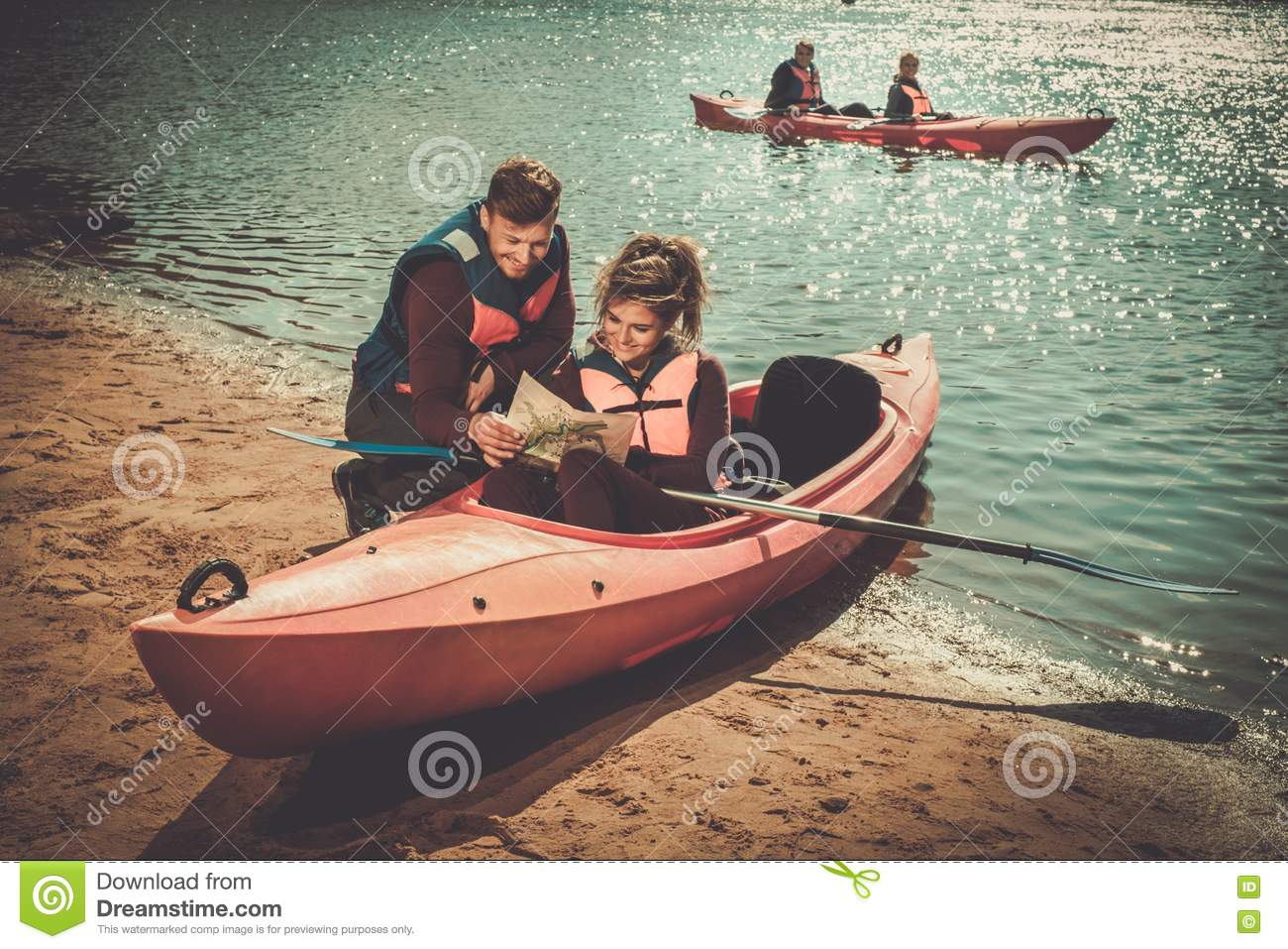 Couple reading a map in kayaks on a beach.