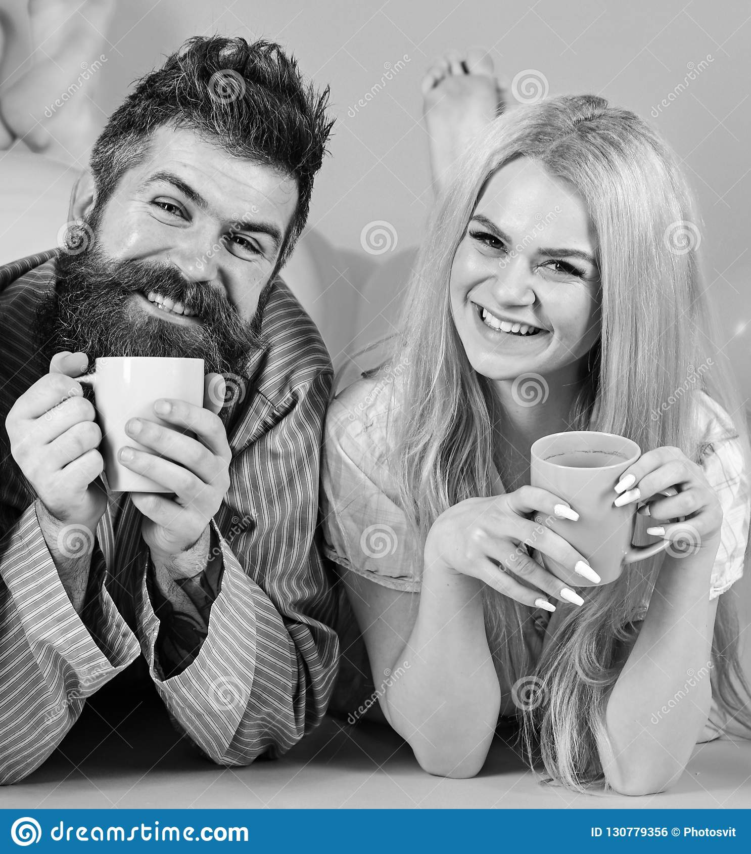 Couple relax in morning with coffee. Family tradition concept. Couple in love drink coffee in bed. Man and woman in