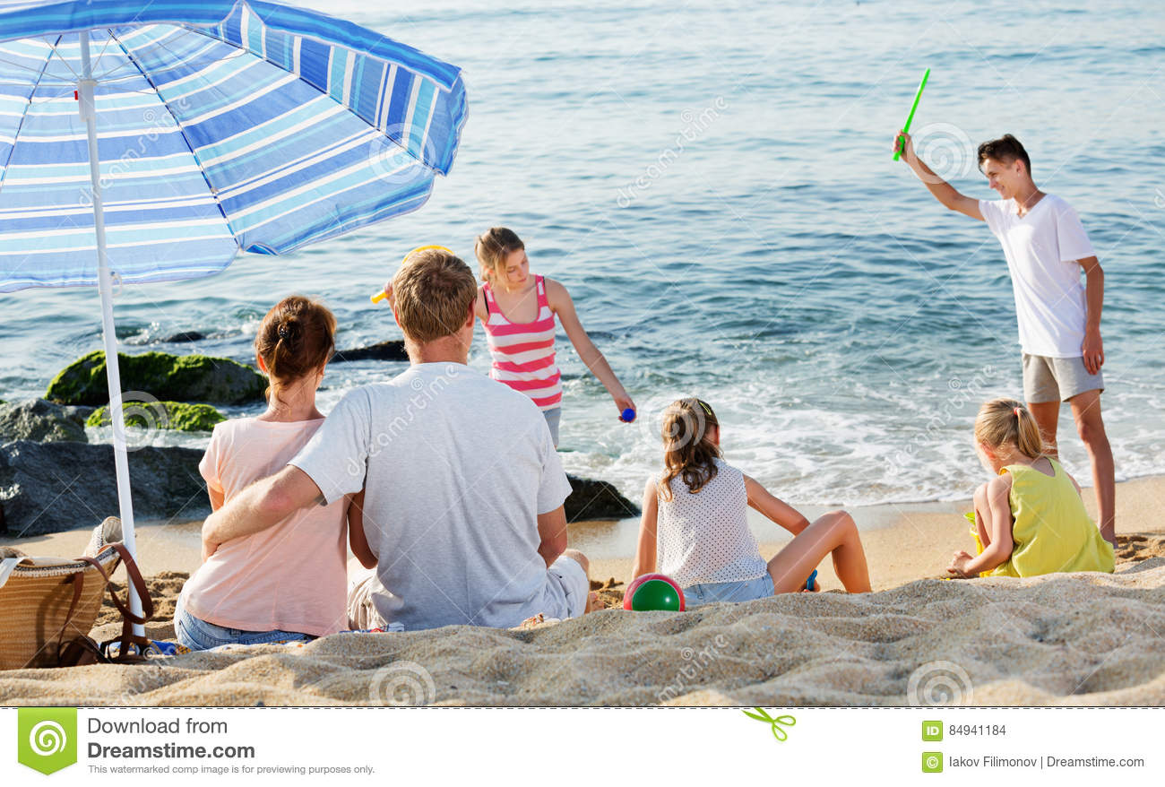 Couple relaxing on beach while their kids playing active games
