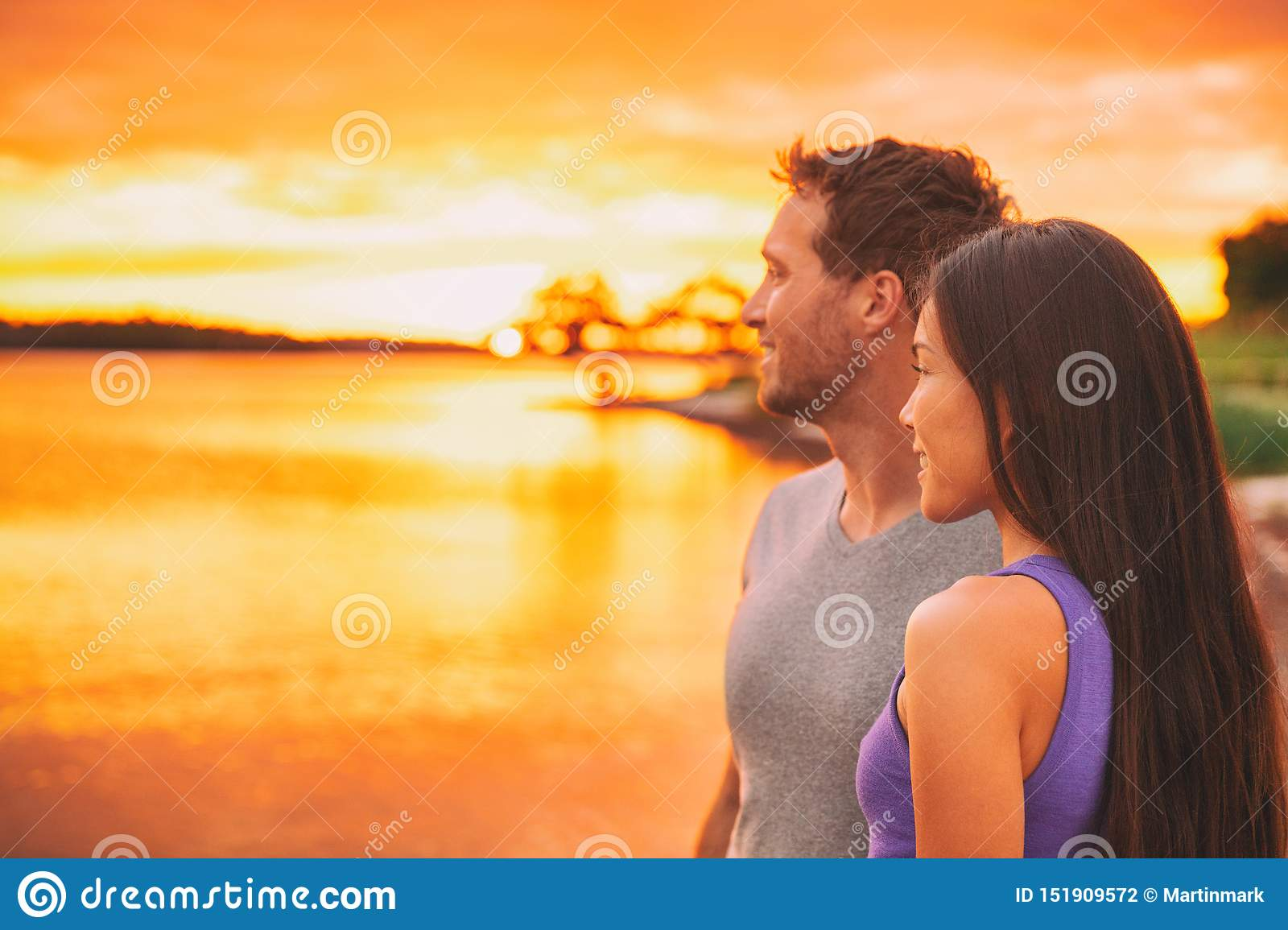 Couple relaxing on beach watching sunset glow over ocean in Caribbean background. Asian girl, Caucasian man interracial