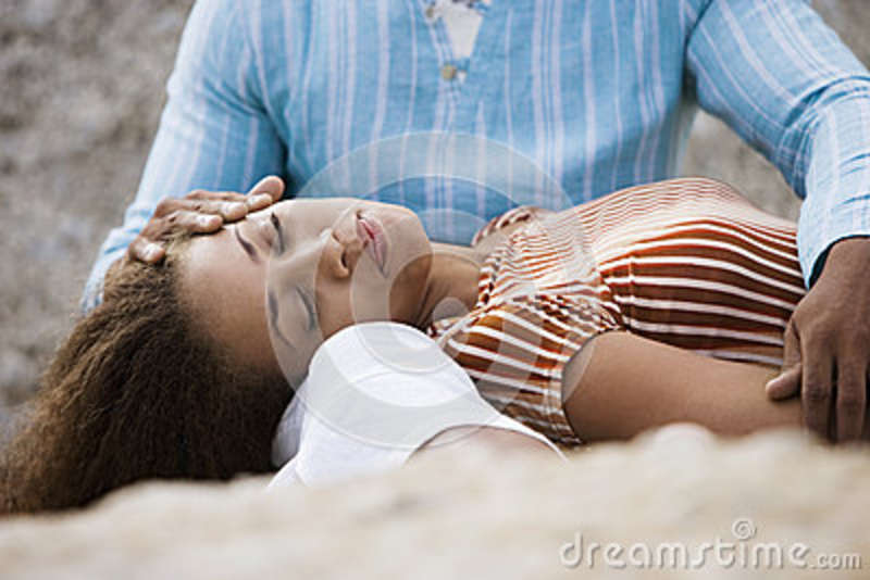 Couple relaxing on beach, woman lying in man s lap, eyes closed, close-up, surface level