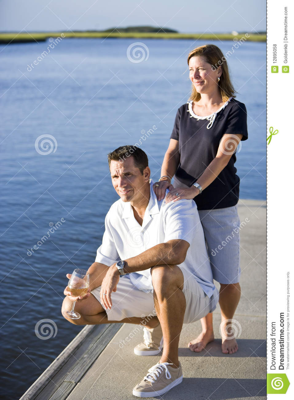 Couple Relaxing With Drink On Dock By Water Royalty Free Stock Photos ...