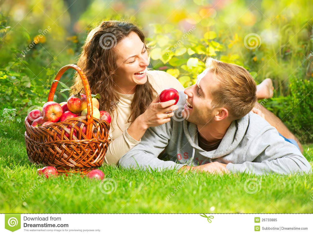 Couple Relaxing on the Grass and Eating Apples