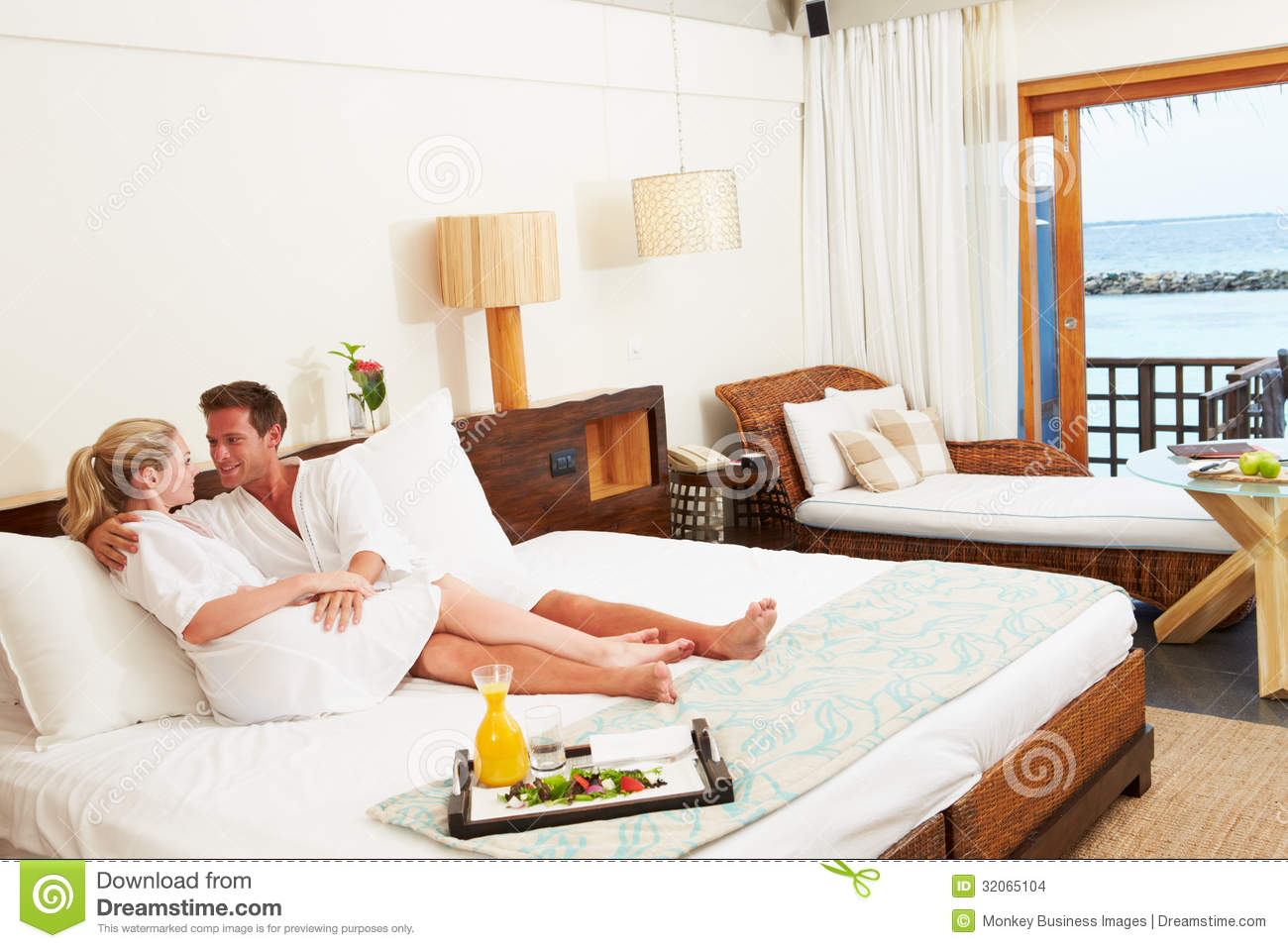 Couple Relaxing In Hotel Room Wearing Robes Stock Images