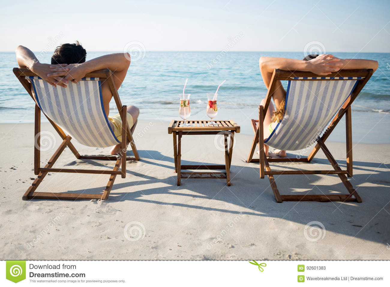 couple relaxing on lounge chairs at beach stock photo - Beach Lounge Chairs