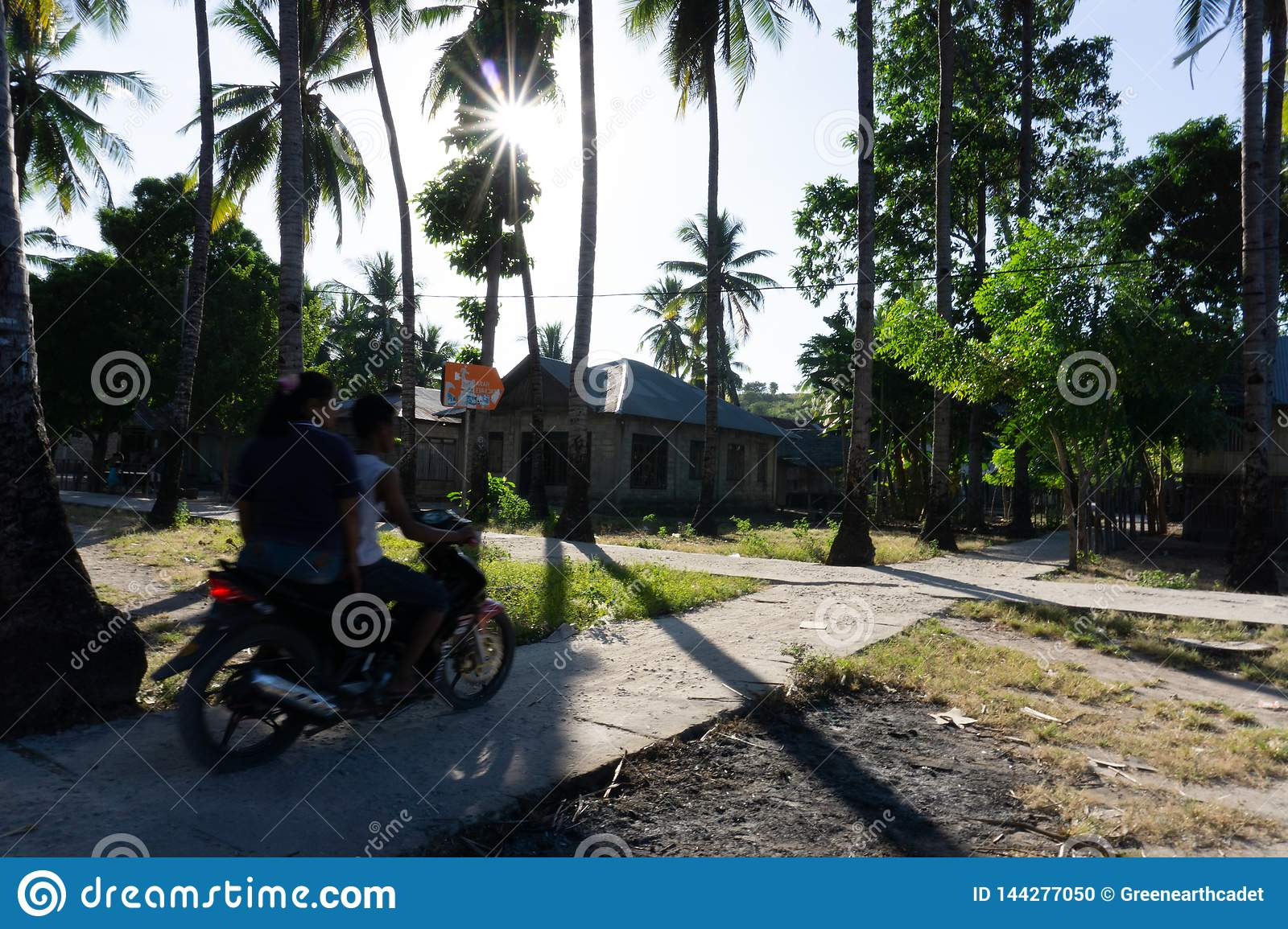 A Couple ride motor cycle on the village road
