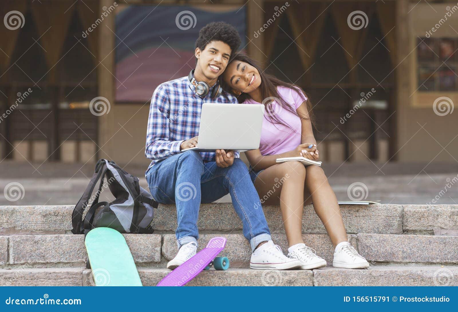 Couple of romantic teens enjoying browsing internet on laptop outdoors