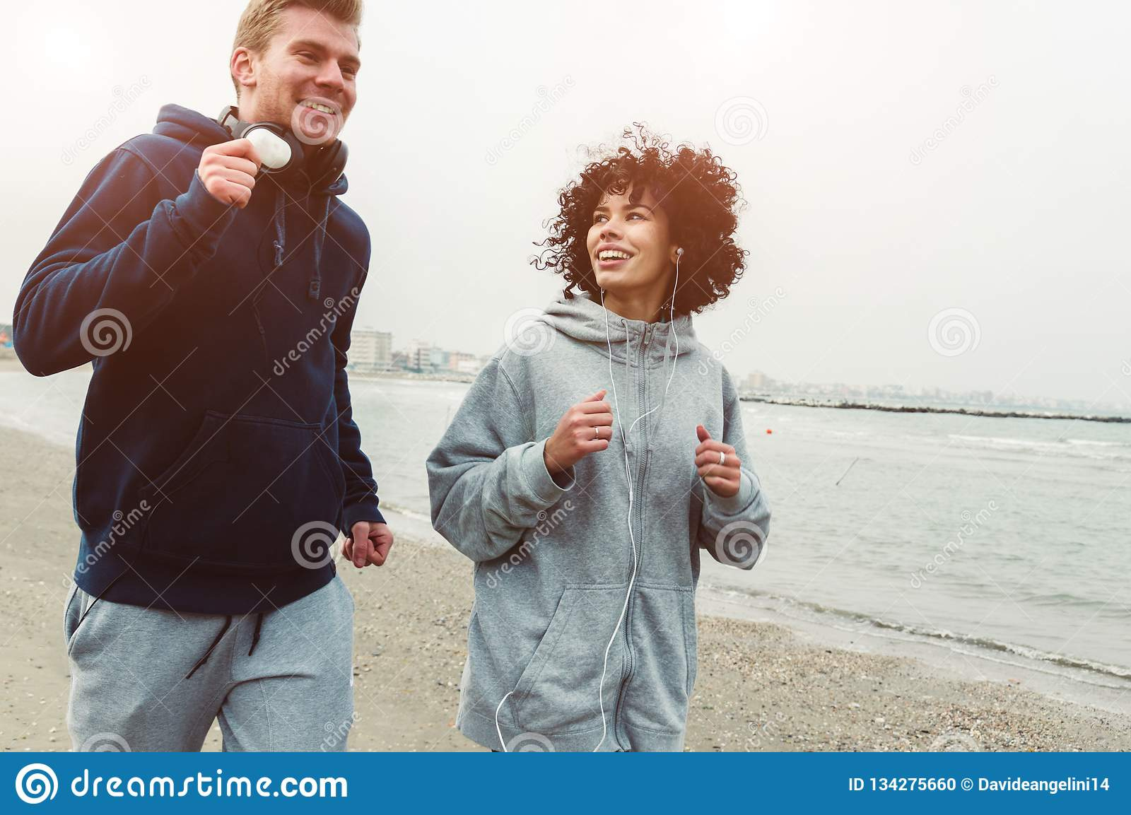 Couple of runners training at the beach in winter