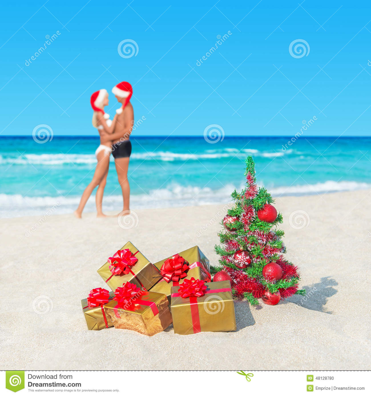 couple in santa hats at tropical beach with christmas tree and stock
