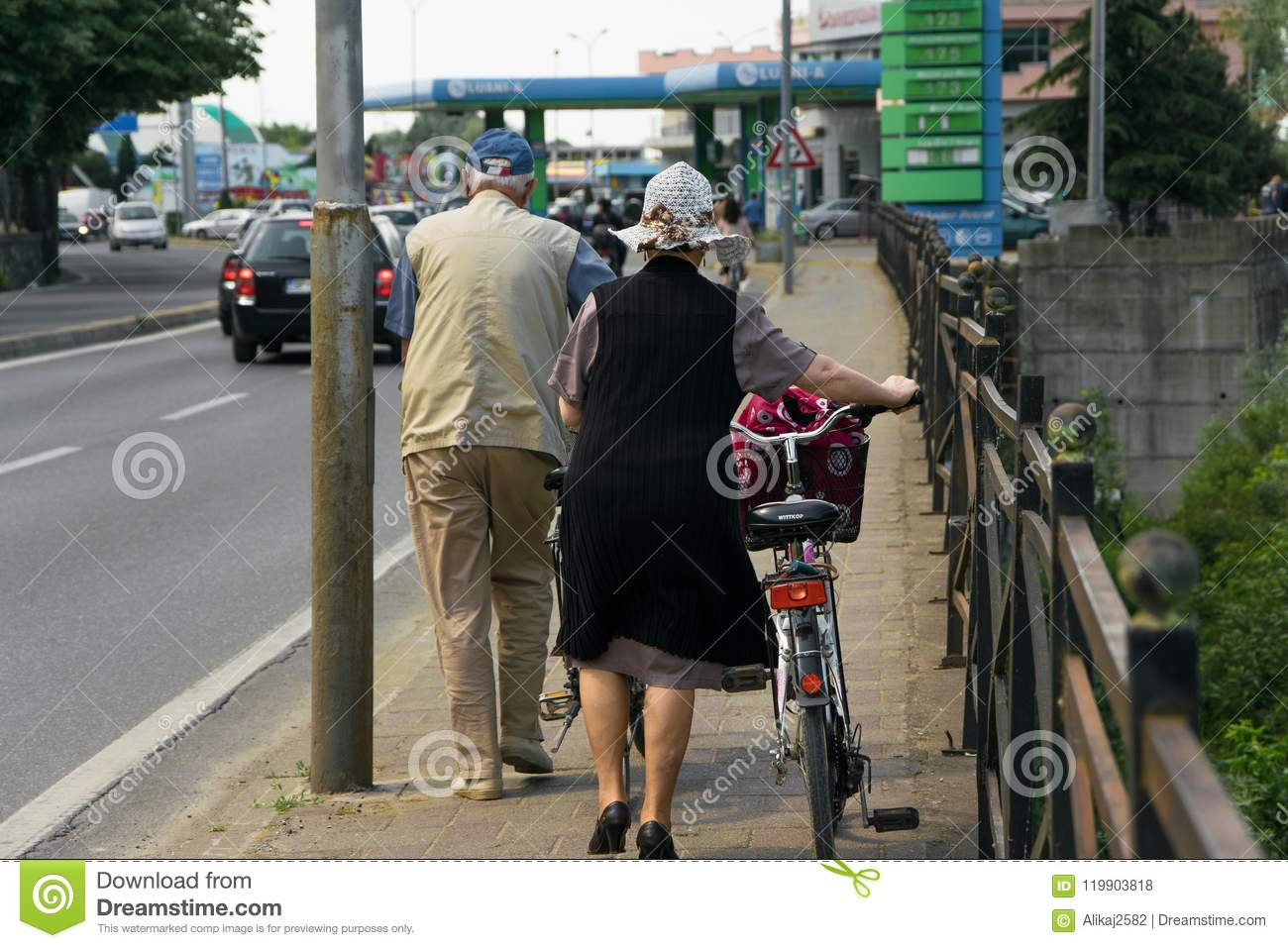 Couple of senior adult walk with bicycles