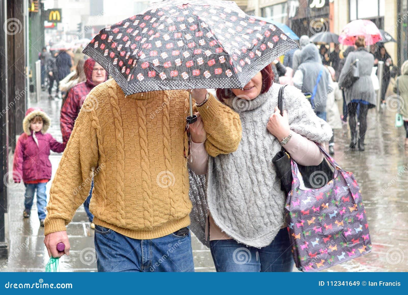 Couple shelter under umbrella In Heavy Rain in the ,UK.