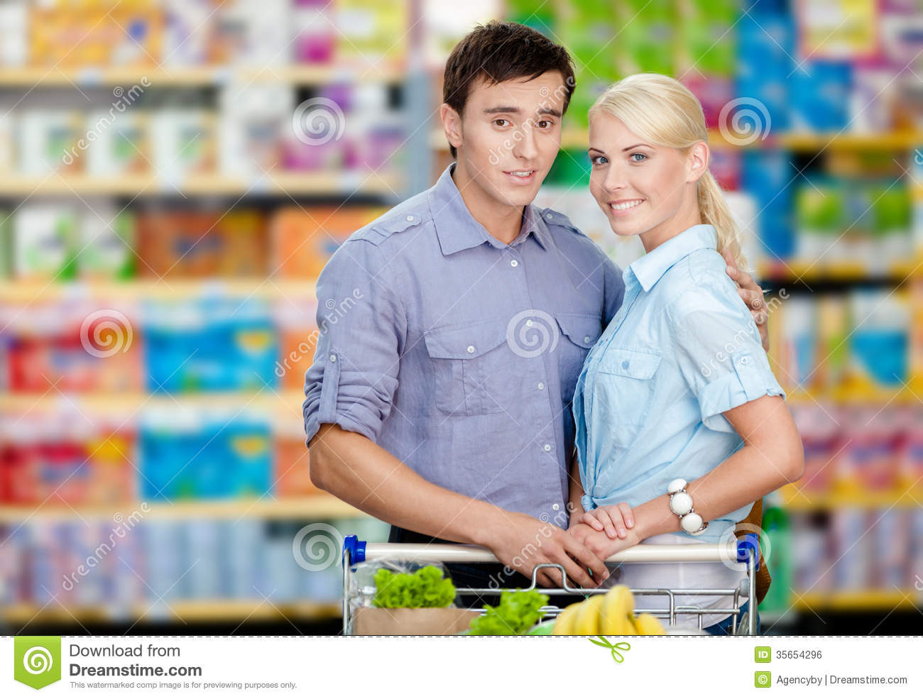 Couple In The Shop With Cart Full Of Food Stock Photo