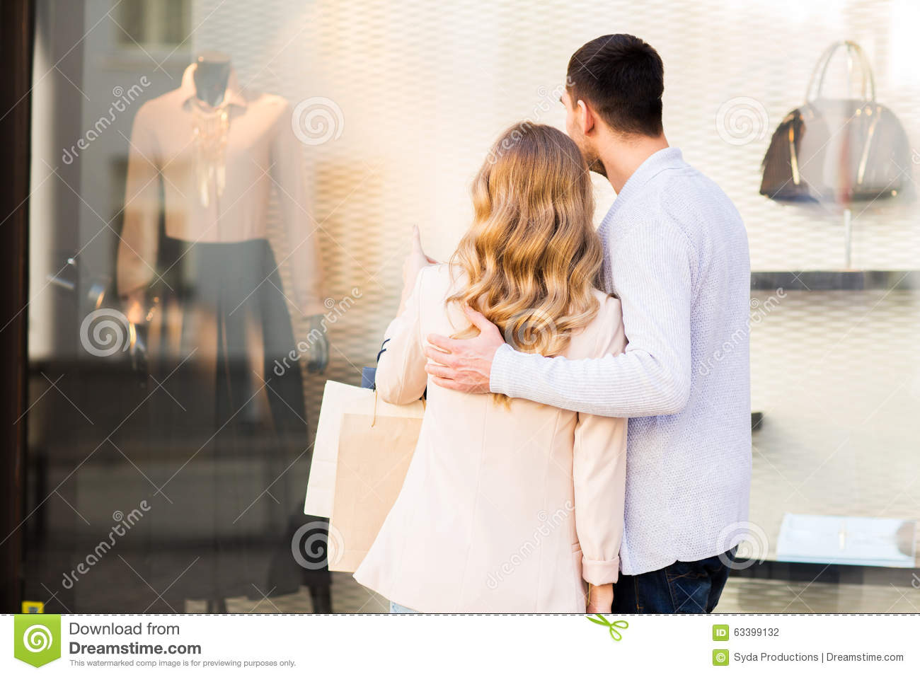 couple with shopping bags looking at shop window stock photo image 63399132. Black Bedroom Furniture Sets. Home Design Ideas