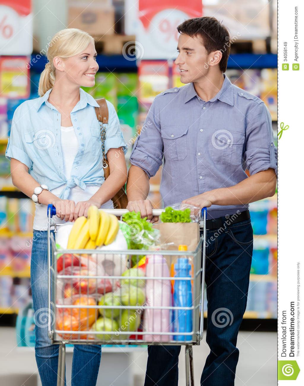 Couple In The Shopping Mall With Cart Full Of Food Stock