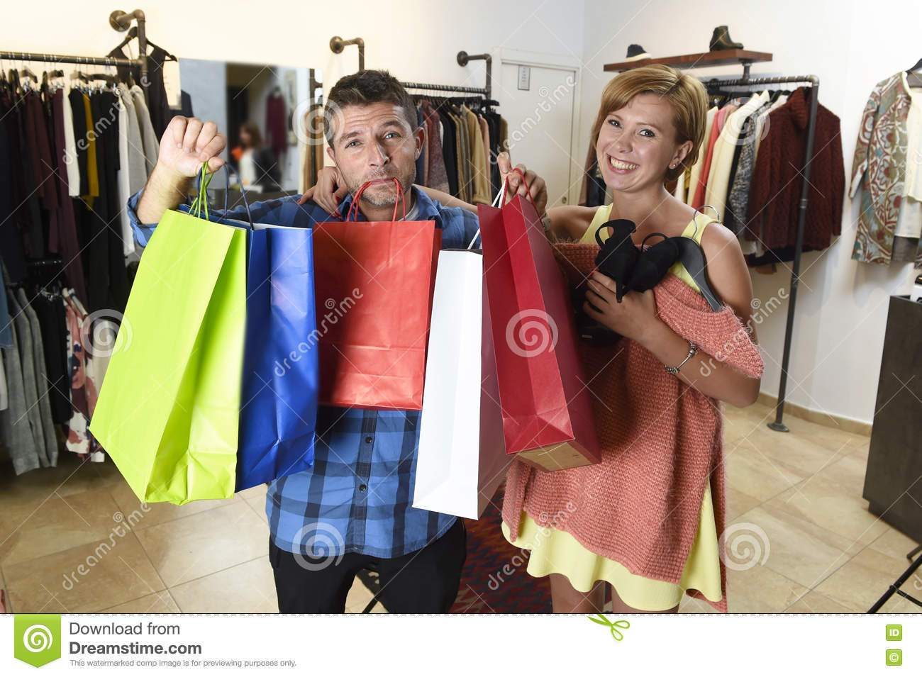 Couple Shopping With Man Tired And Bored Holding Bags And Woman ...