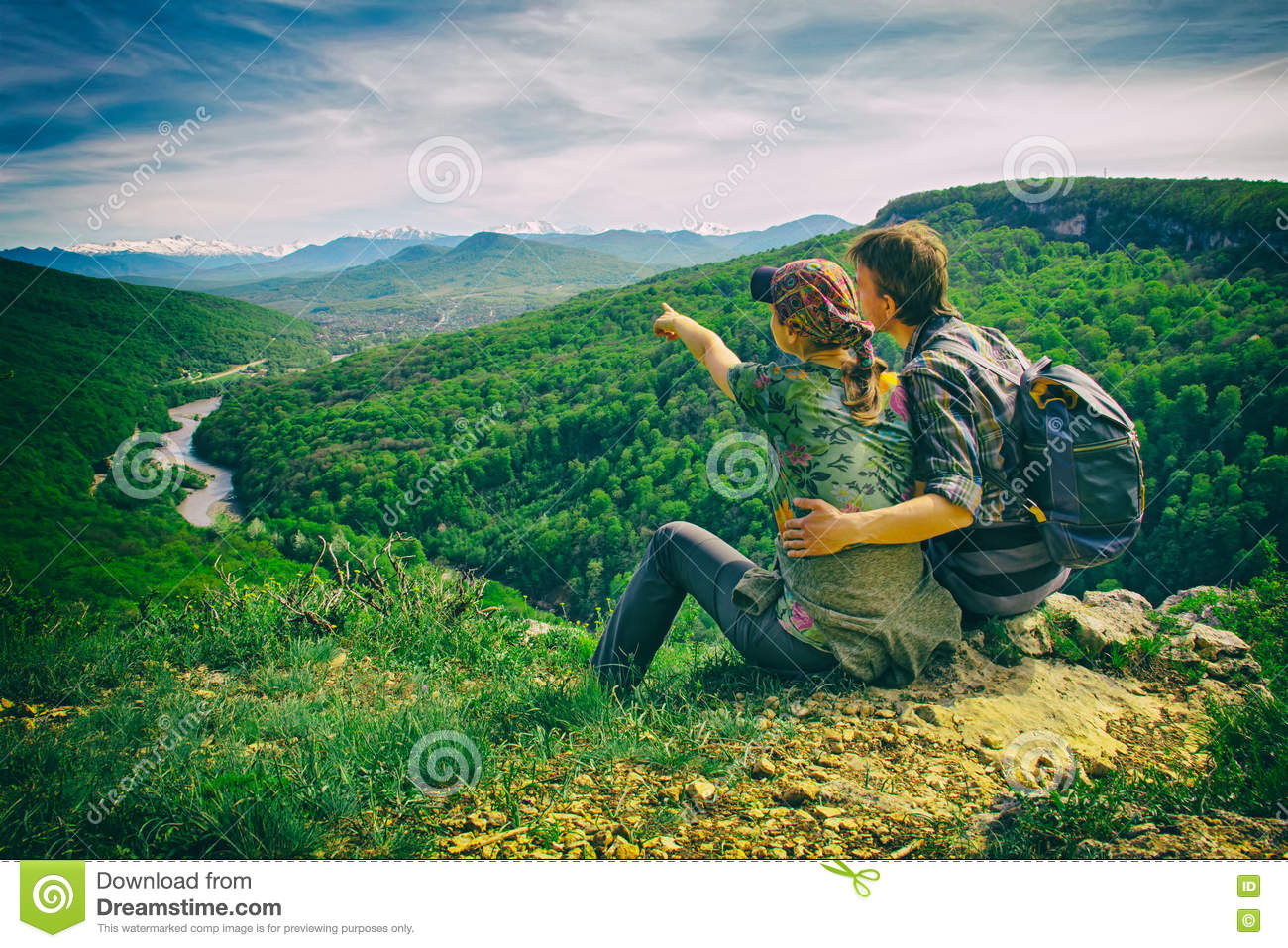 Couple sits on the edge and looks to the mountains, girl points, the effect of the retro camera